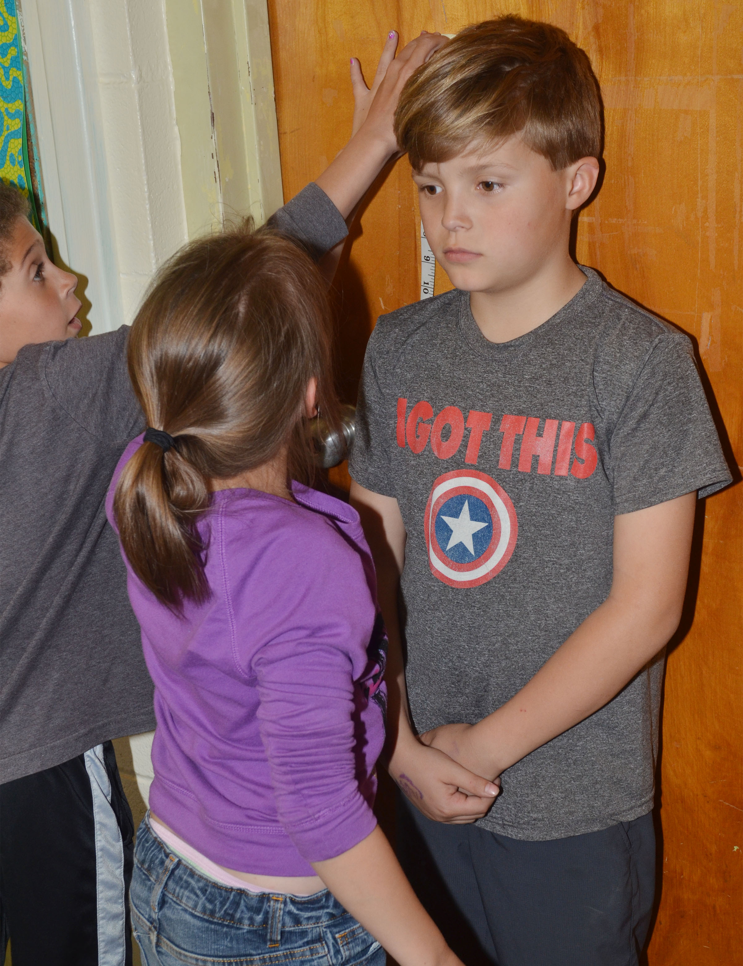 CES second-grader Emerson Gowin stands as his classmates Trever Lasley, at left, and Alyah Meadows measure him.