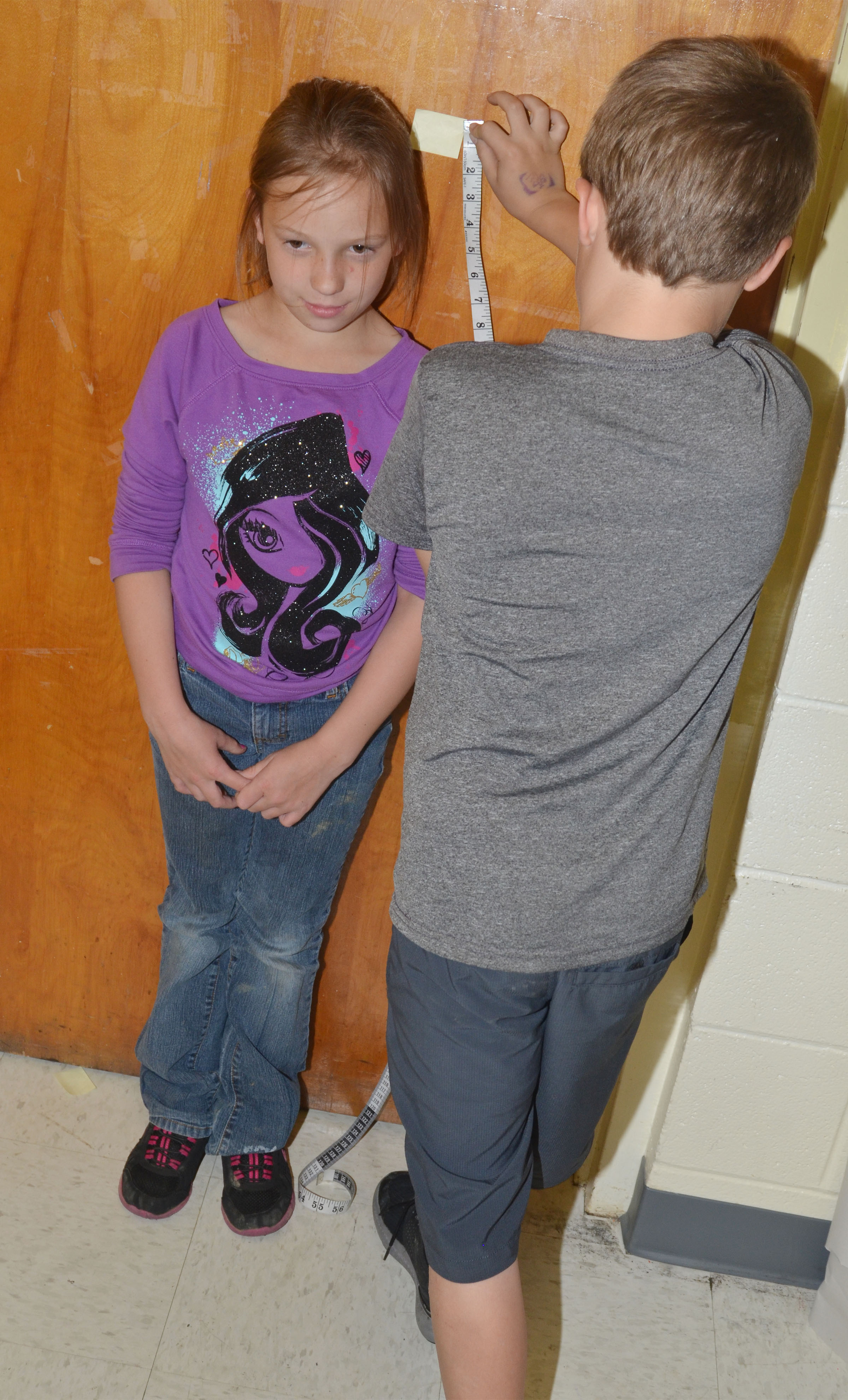 CES second-grader Emerson Gowin measures classmate Alyah Meadows.