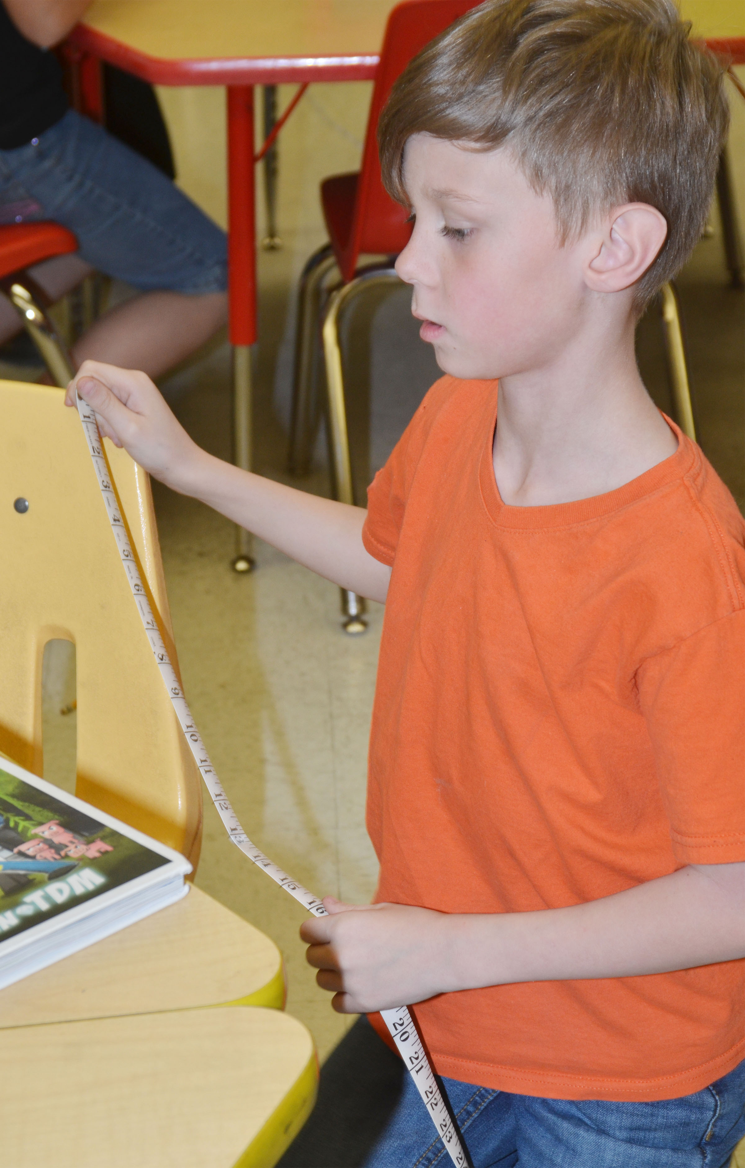 CES second-grader Isaya Adams measures the height of his chair.