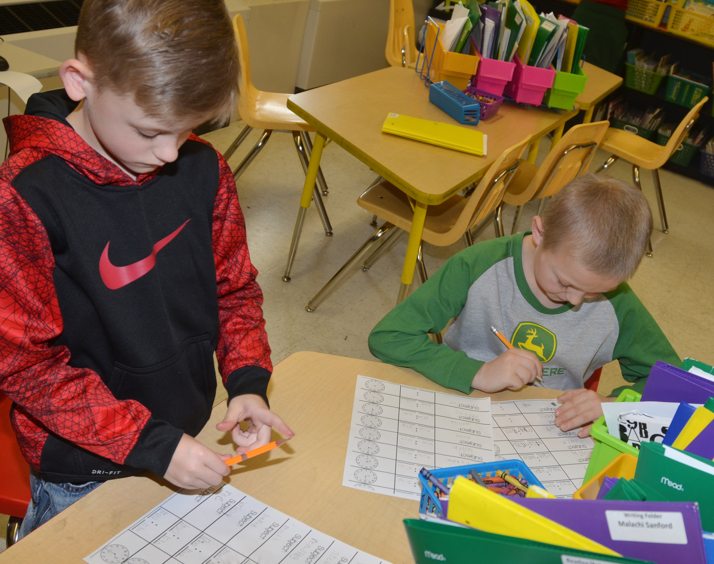 CES second-graders Malachi Sanford, at left, and Trenton Harris write a schedule of their day to help them tell time.