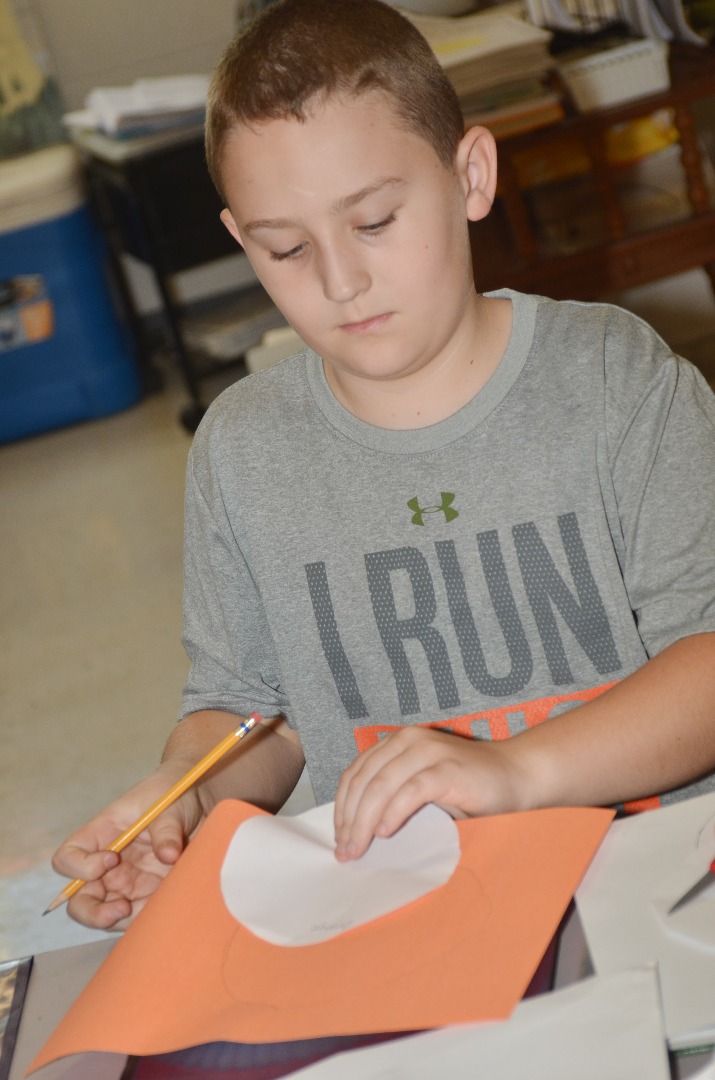 CES third-grader Carson Ford traces a circle for his absolute location diagram.