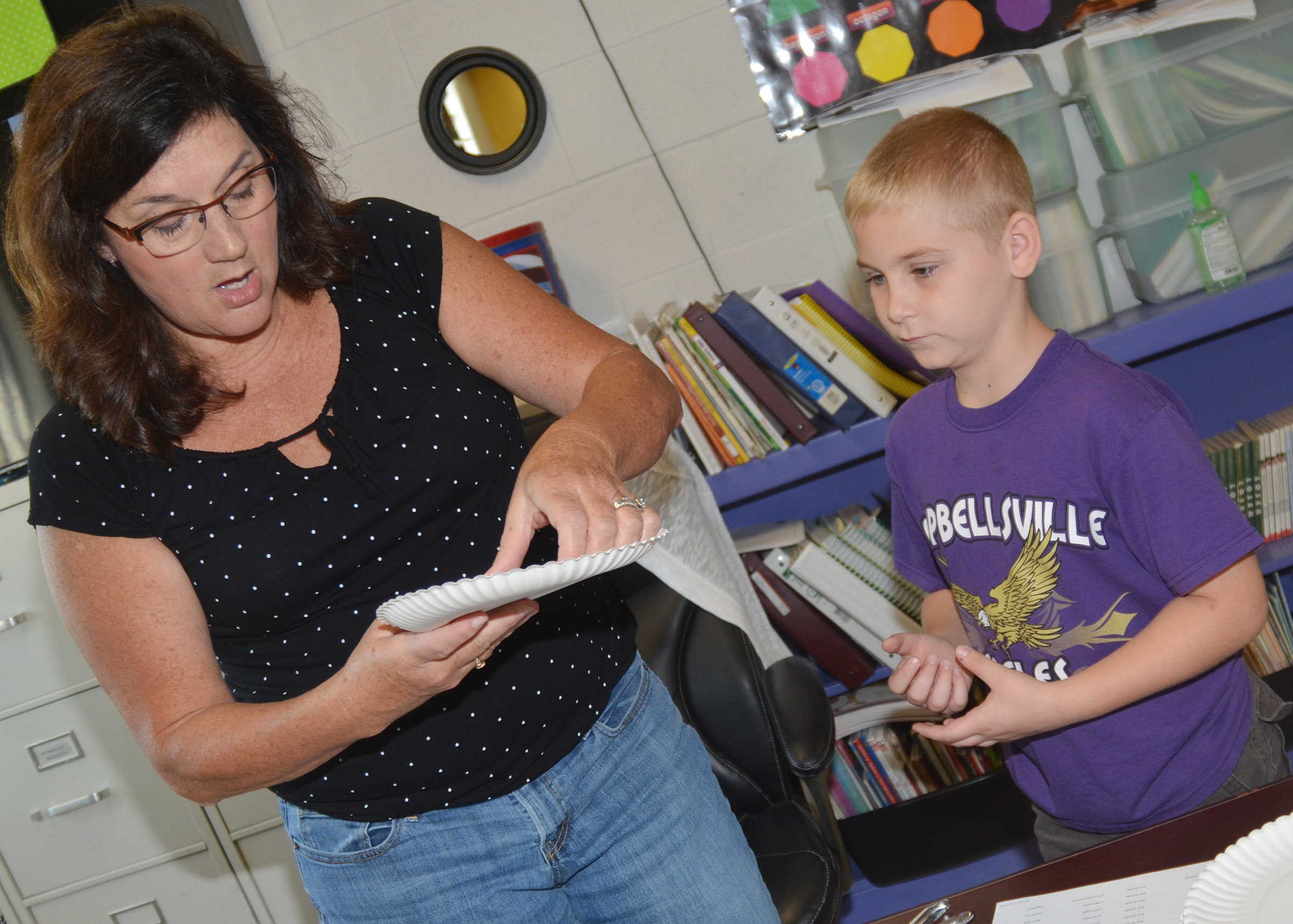 CES teacher Patty Haley helps third-grader Joseph Greer put together his absolute location diagram.