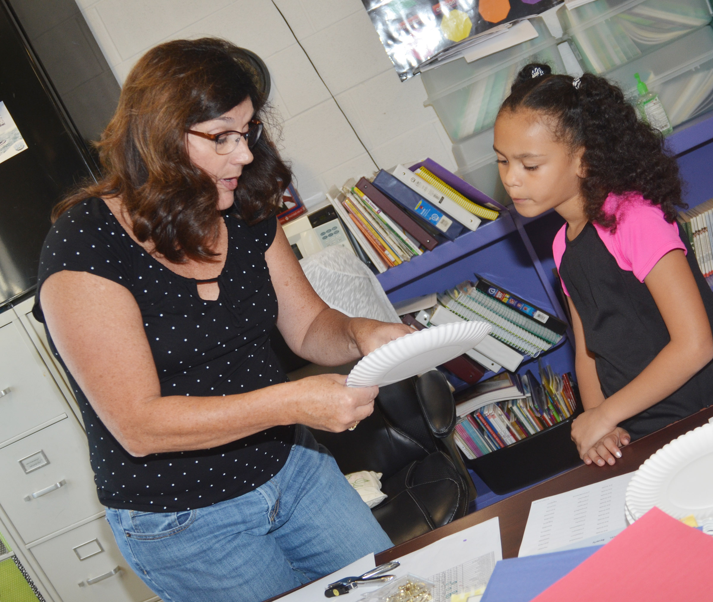 CES teacher Patty Haley helps third-grader Alexia Howard put her absolute location diagram together.