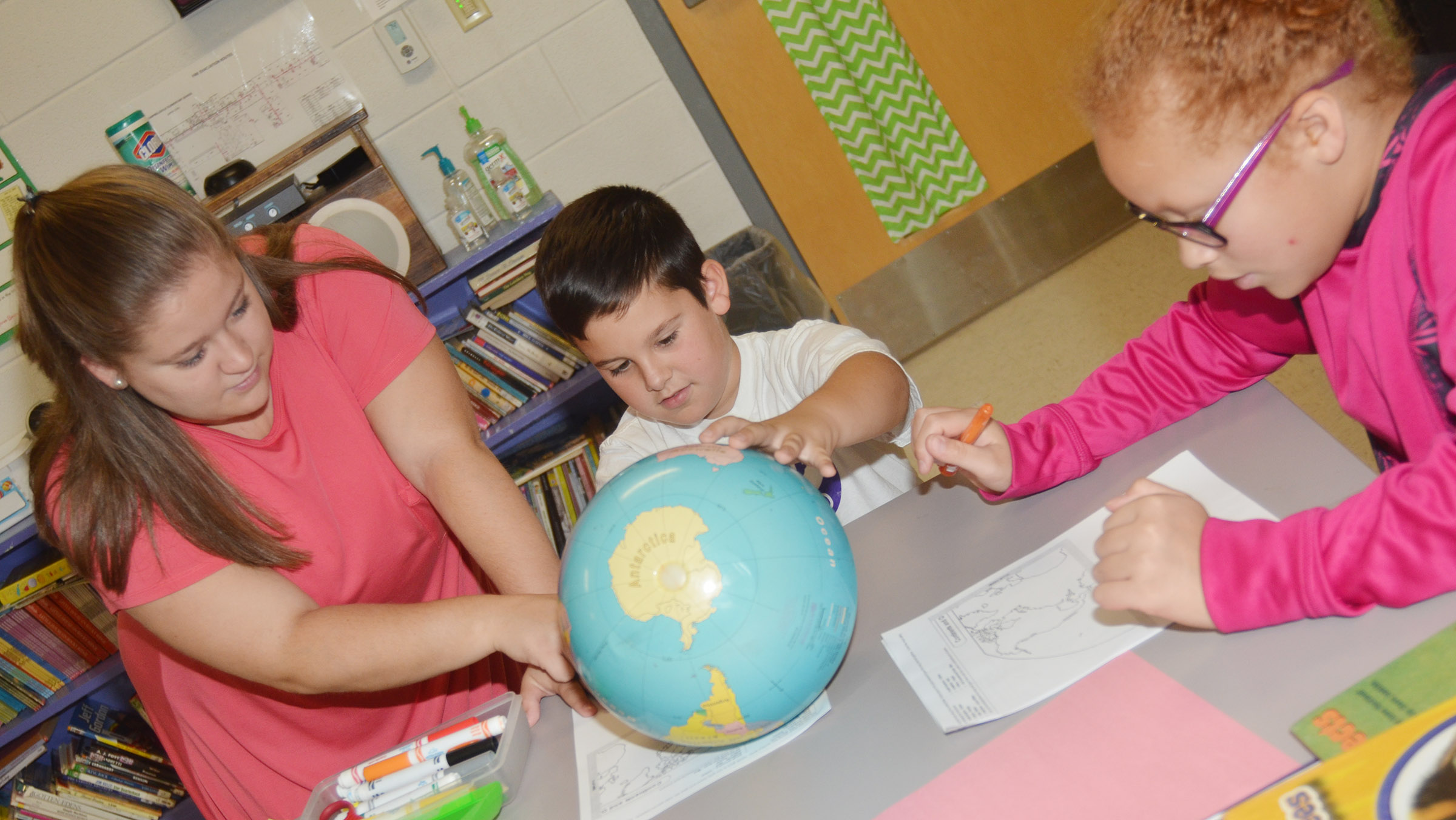 Campbellsville University education student Jordan Bray helps third-grader Damien Clark find the continents on a globe, as his classmate Kallie Taylor works to identify them on her worksheet.