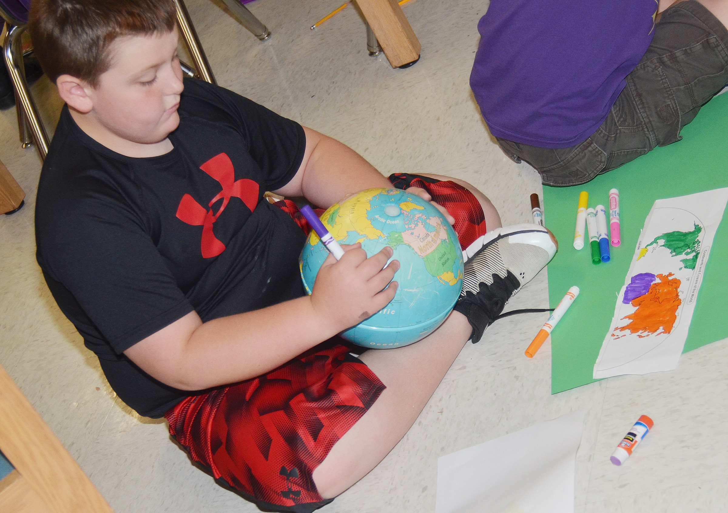 CES third-grader Braxton Tucker uses a globe to help him label the continents.