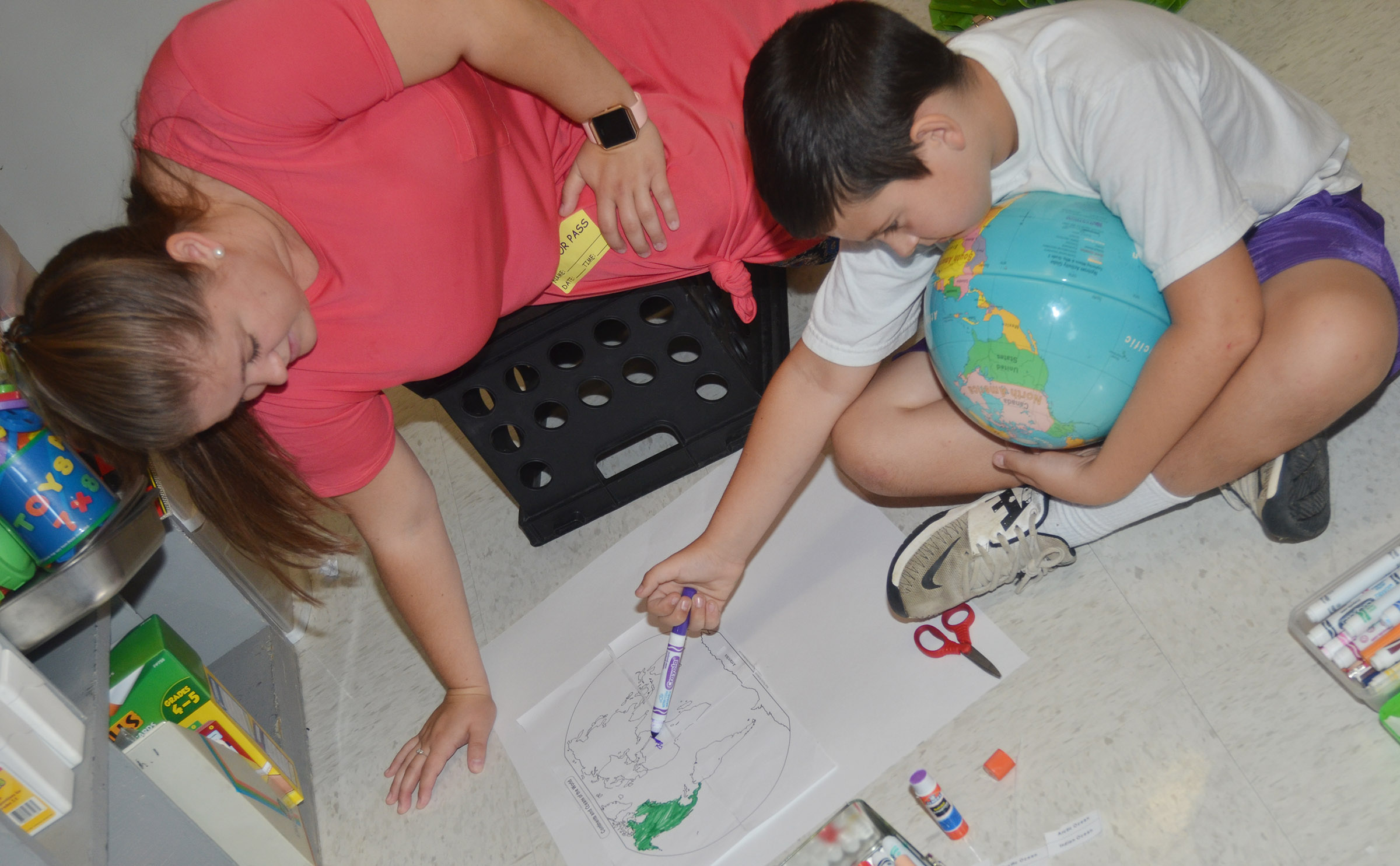 Campbellsville University education student Jordan Bray helps third-grader Damien Clark label the continents.