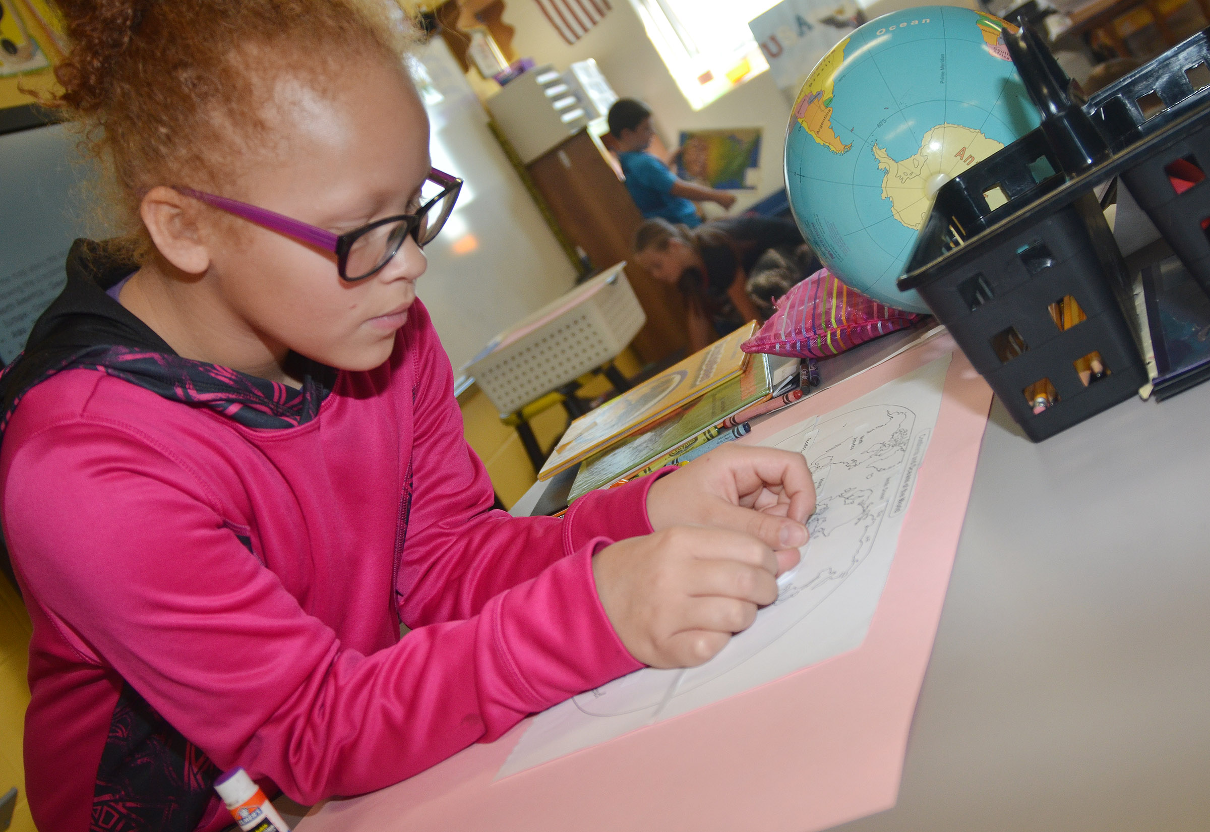 CES third-grader Kallie Taylor labels the continents.