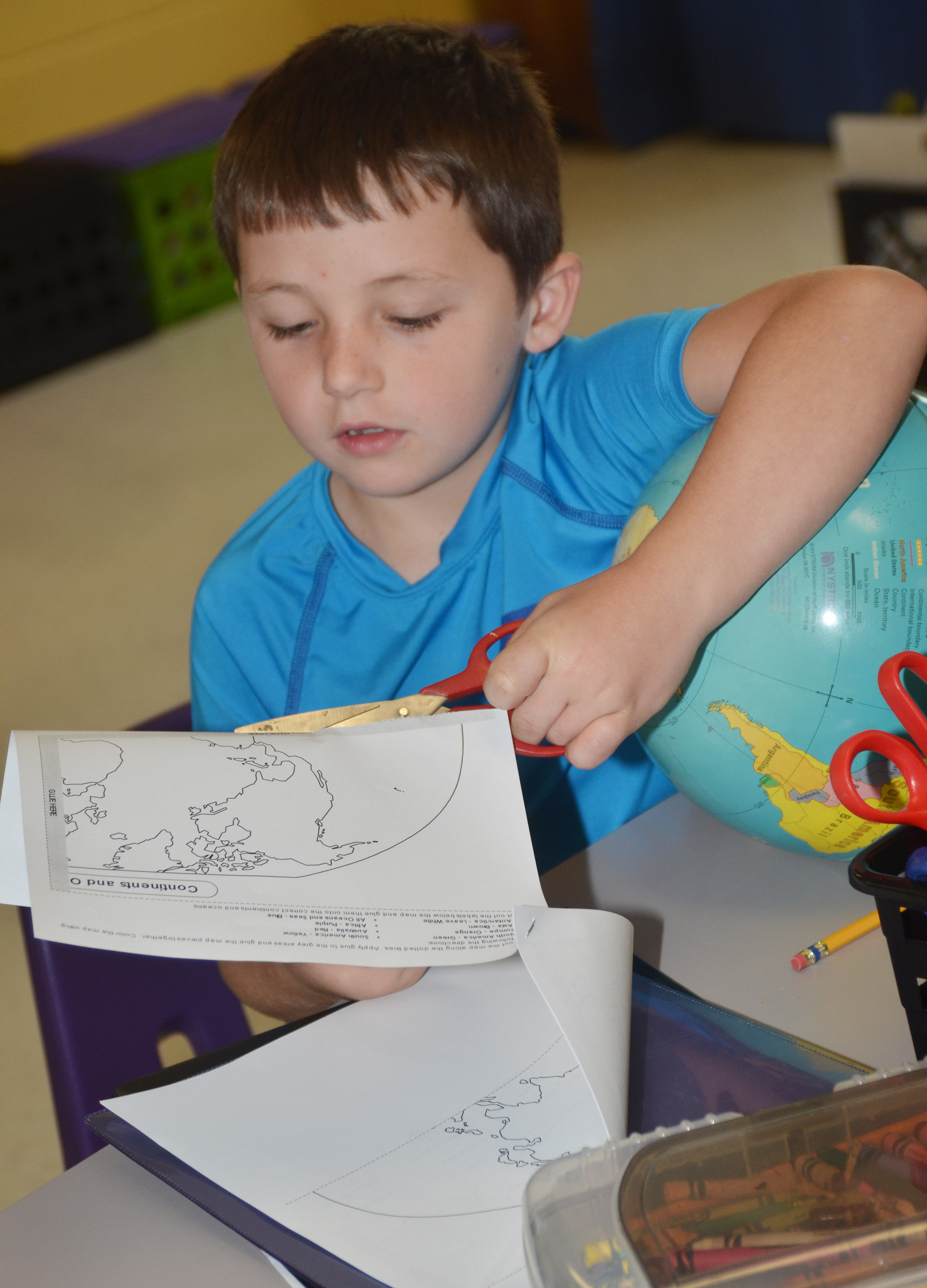 CES third-grader Codey Parks cuts out his continents to glue on construction paper.