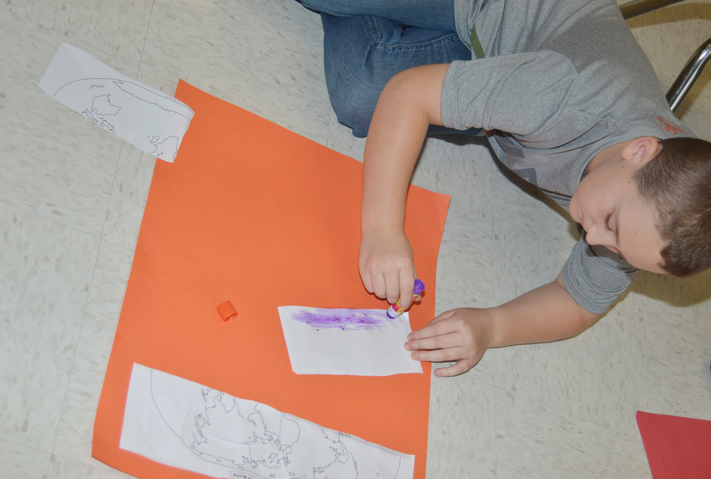 CES third-grader Carson Ford glues his continents on construction paper.