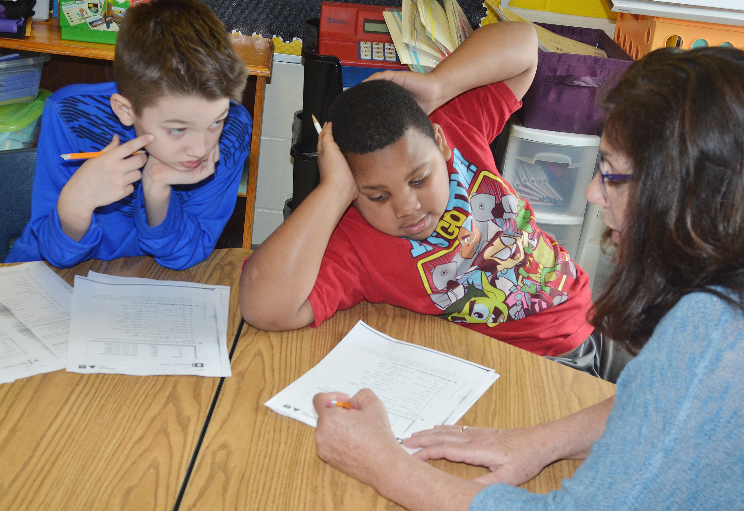 CES third-grade teacher Patty Haley works with students Landon Tucker, at left, and Malikiah Spurling to learn about irregular verbs.