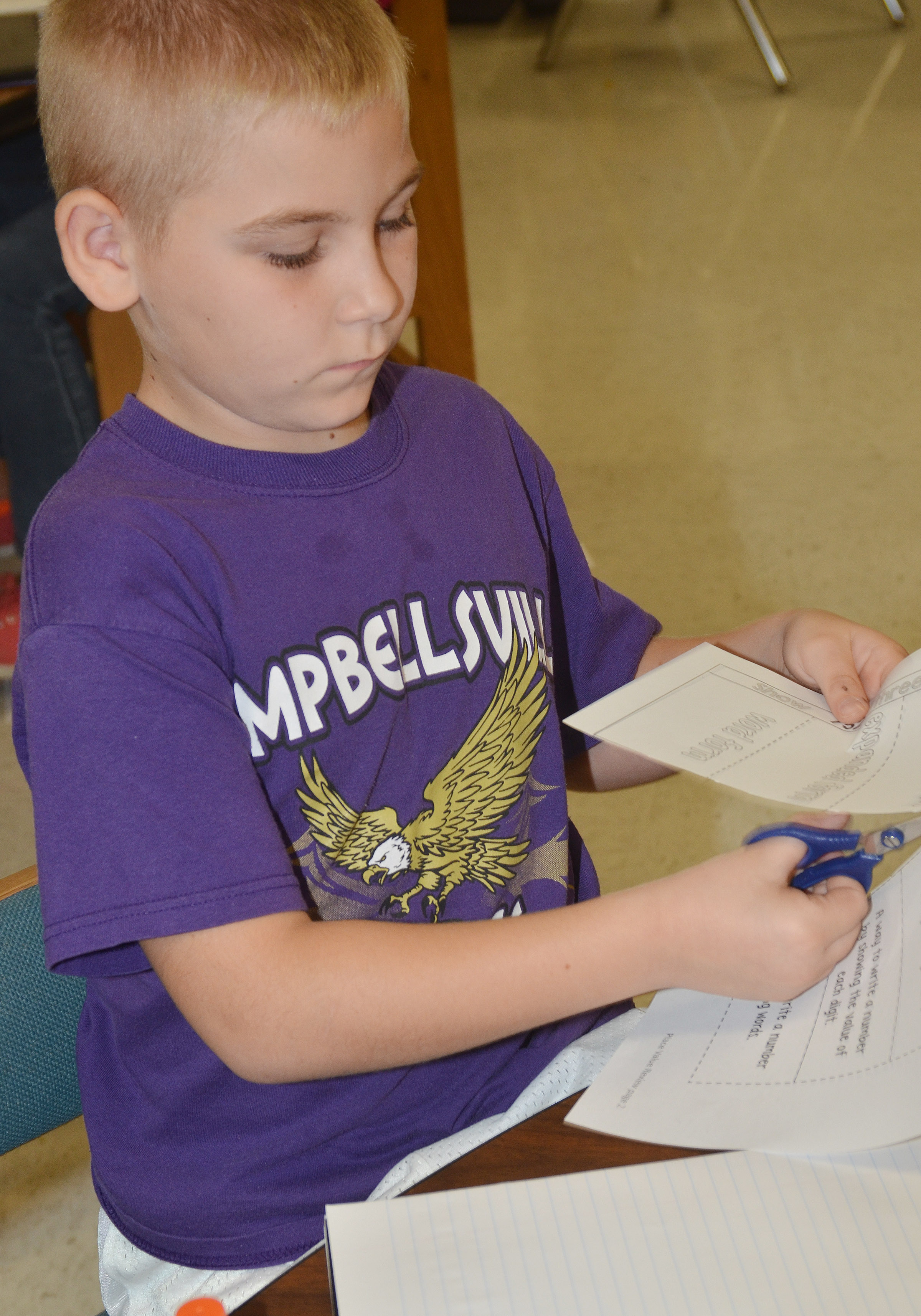 CES third-grader Joseph Greer makes his booklet to study number forms.