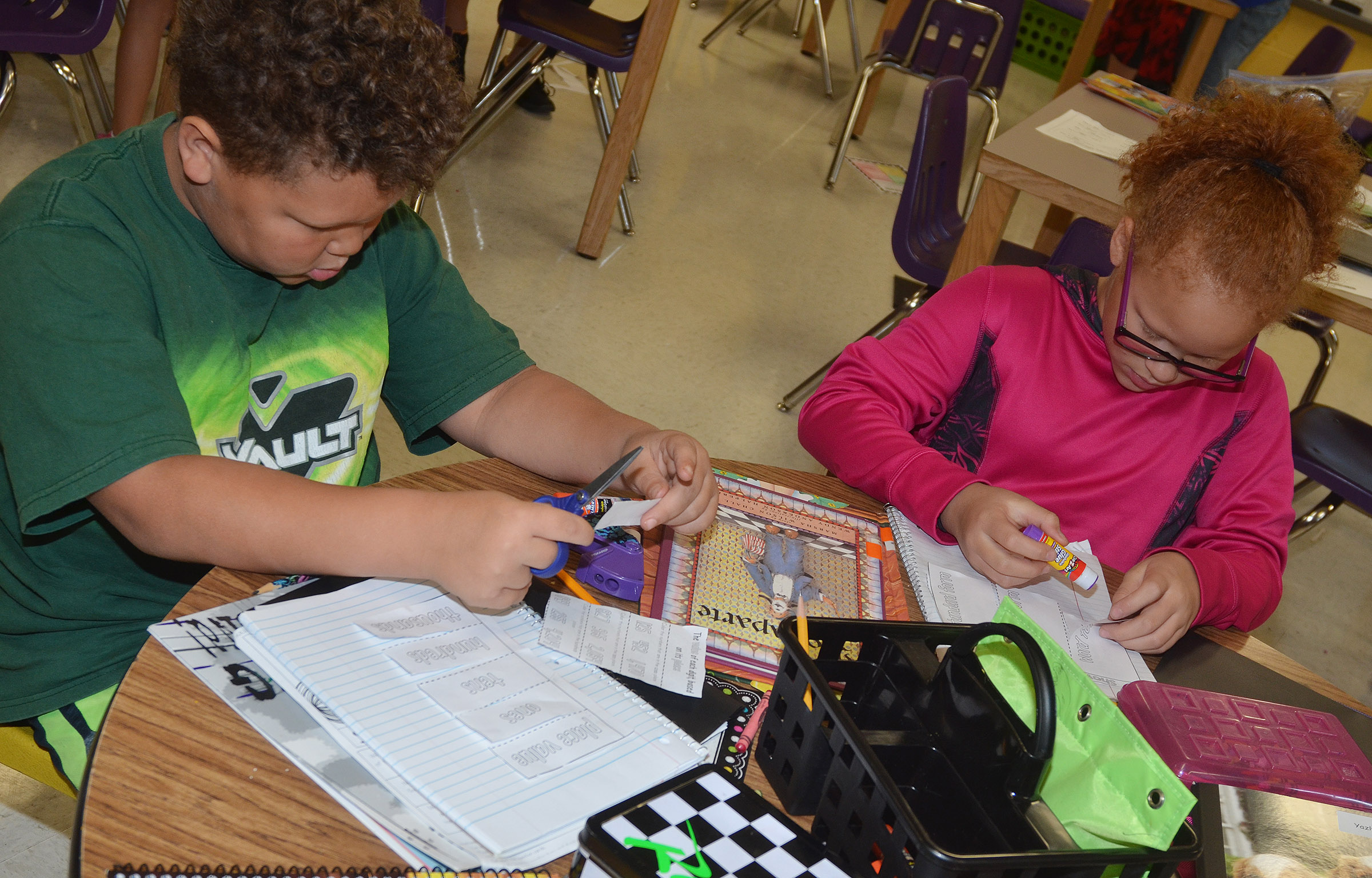 CES third-graders Drevonte Gurley, at left, and Kallie Taylor make their number forms booklet.