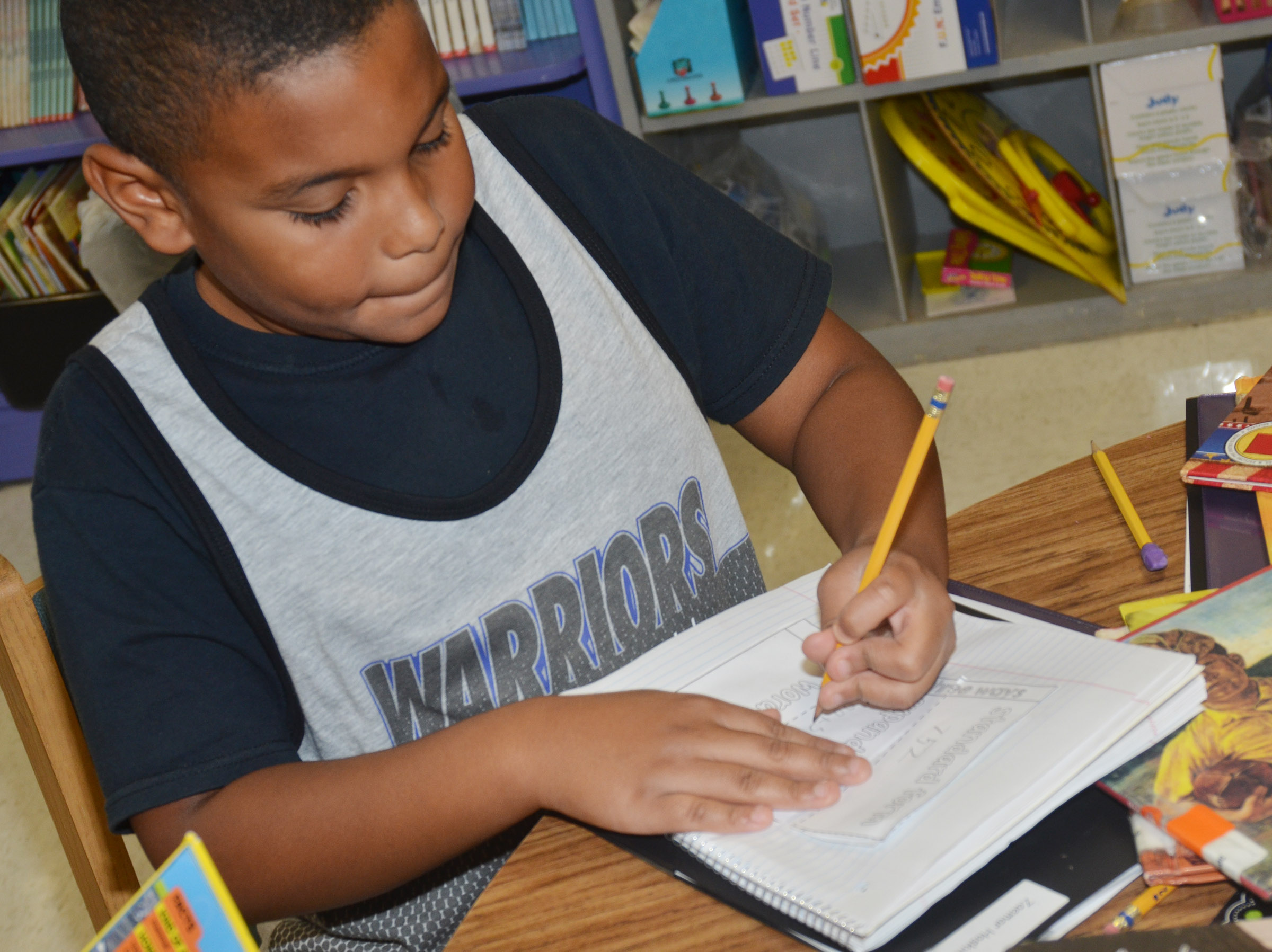 CES third-grader Zaemar Hoskins writes a number in word, expanded and standard forms.