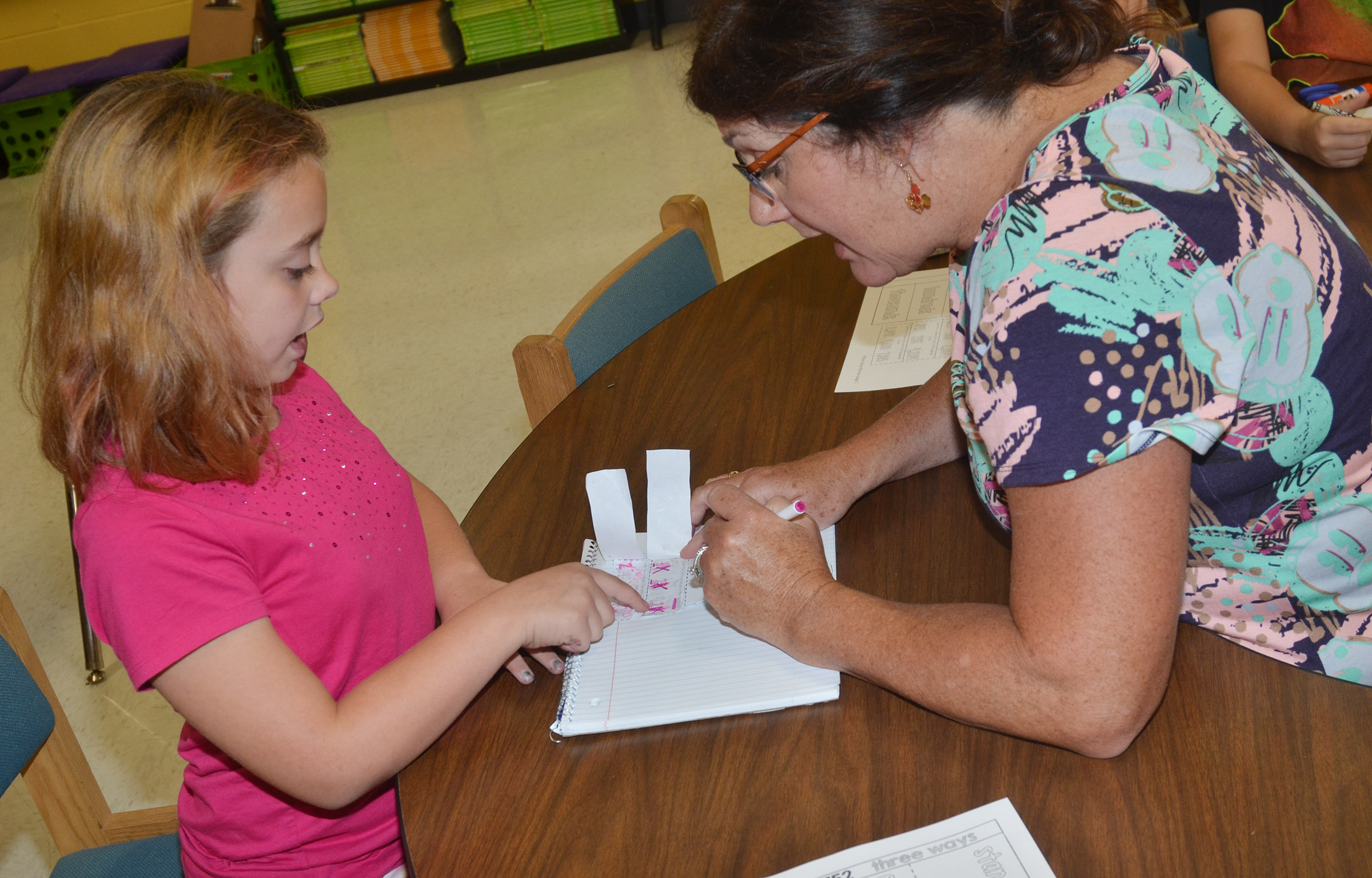 CES teacher Patty Haley helps third-grader Angelina Babbs understand word, expanded and standard forms.