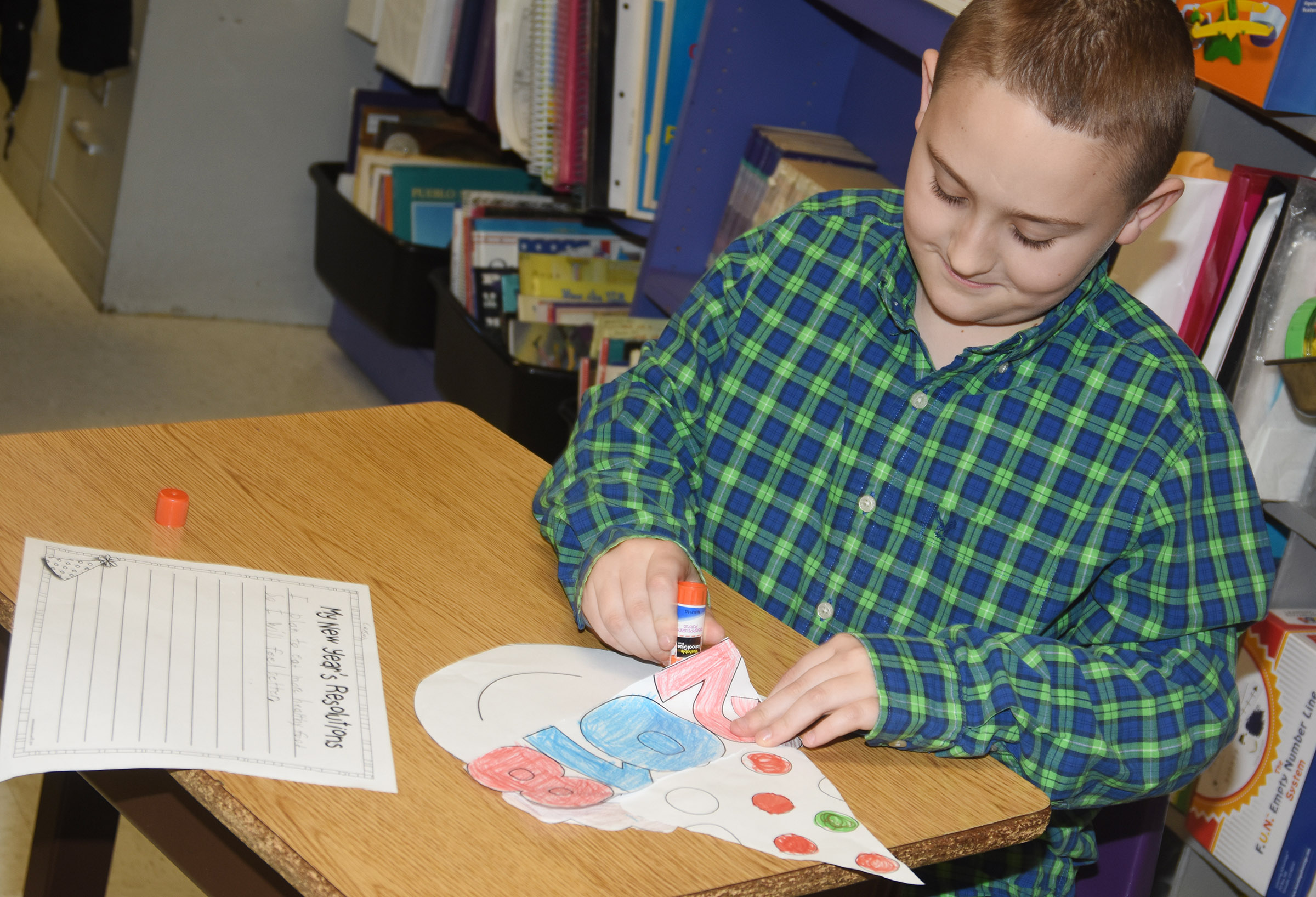CES third-grader Carson Ford glues together his New Year's resolution project.