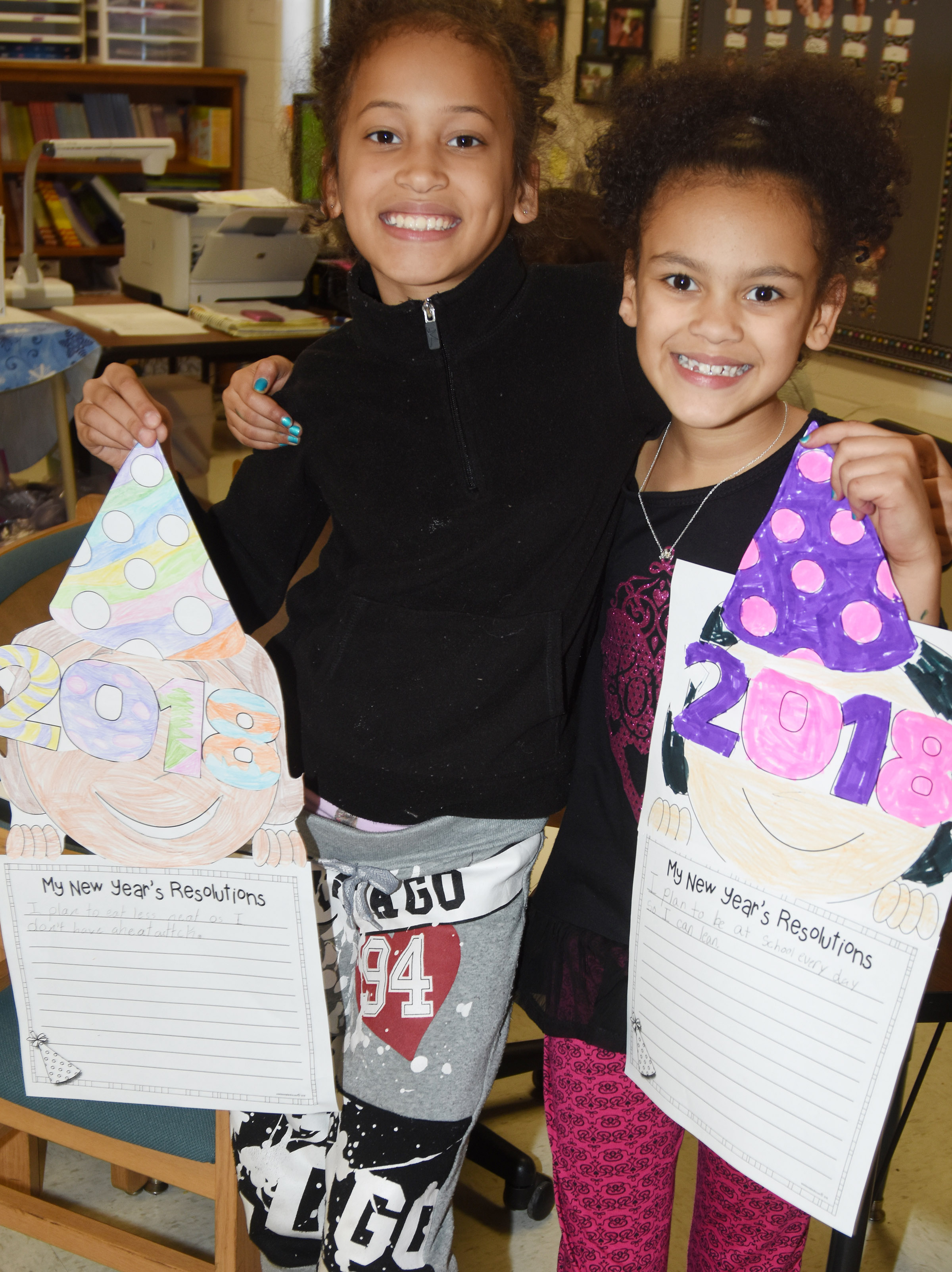CES third-graders Yazlyn Sutton, at left, and Alexia Howard hold their New Year's resolution projects.