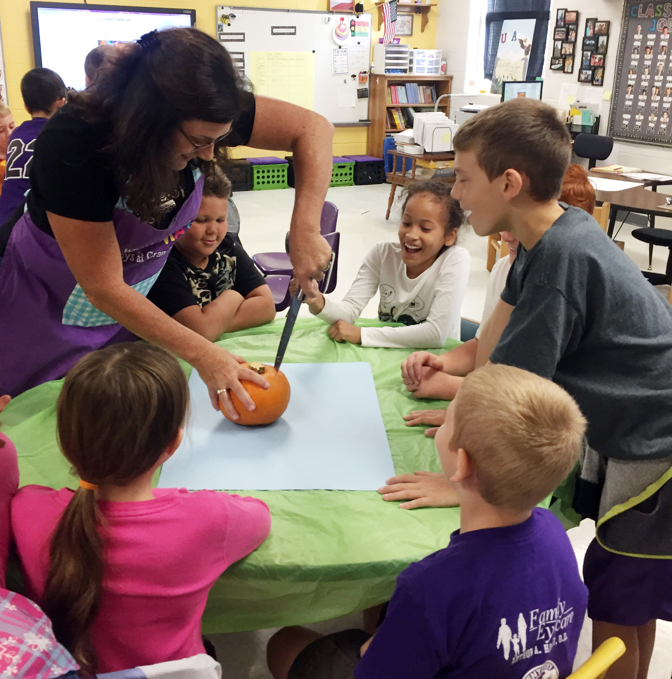 CES third-grade teacher Patty Haley carves a pumpkin for her students.