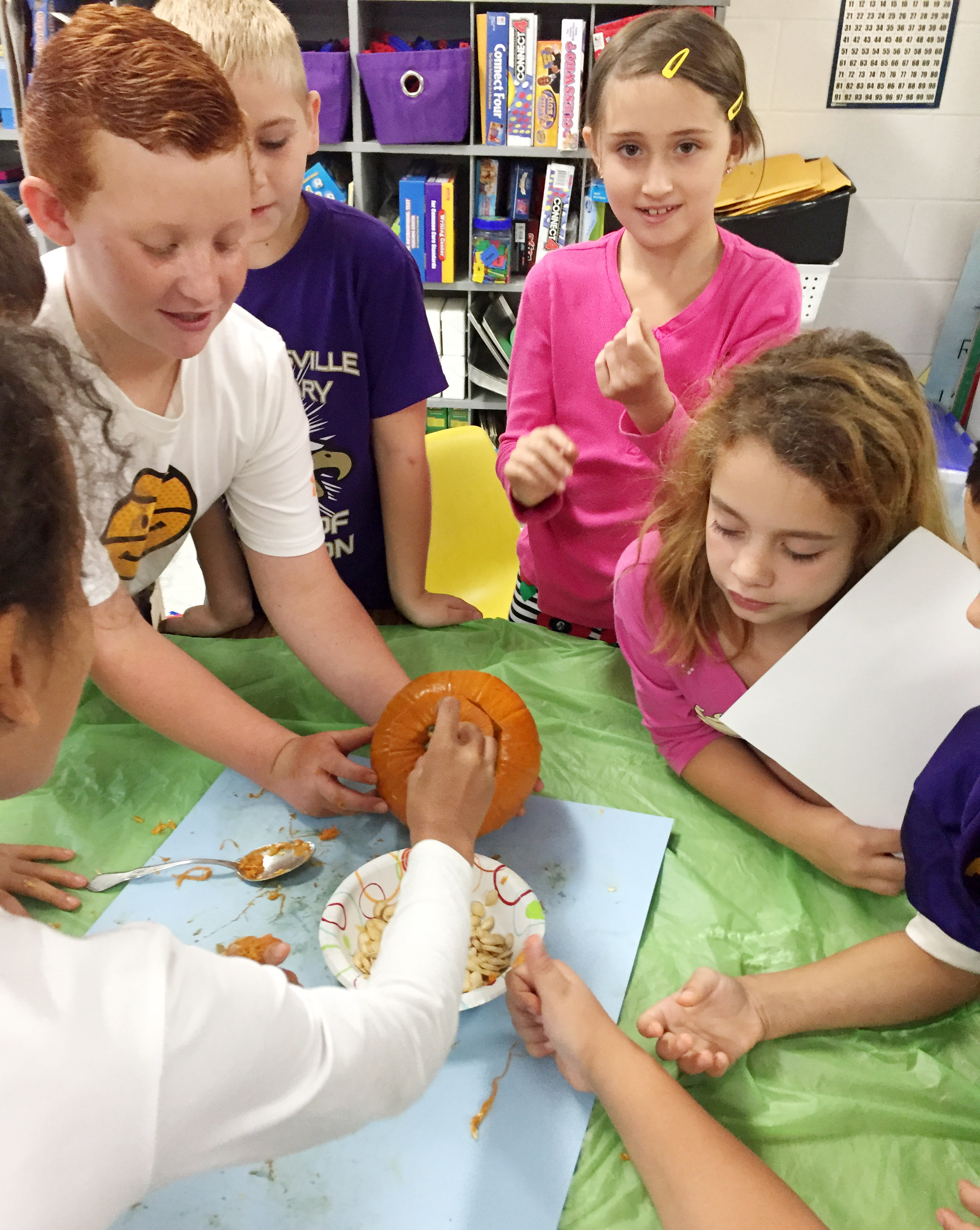 CES third-graders, from left, Reece Swafford, Joseph Greer, Cadence Burton and Angelina Babbs sort their pumpkin seeds with their classmates.