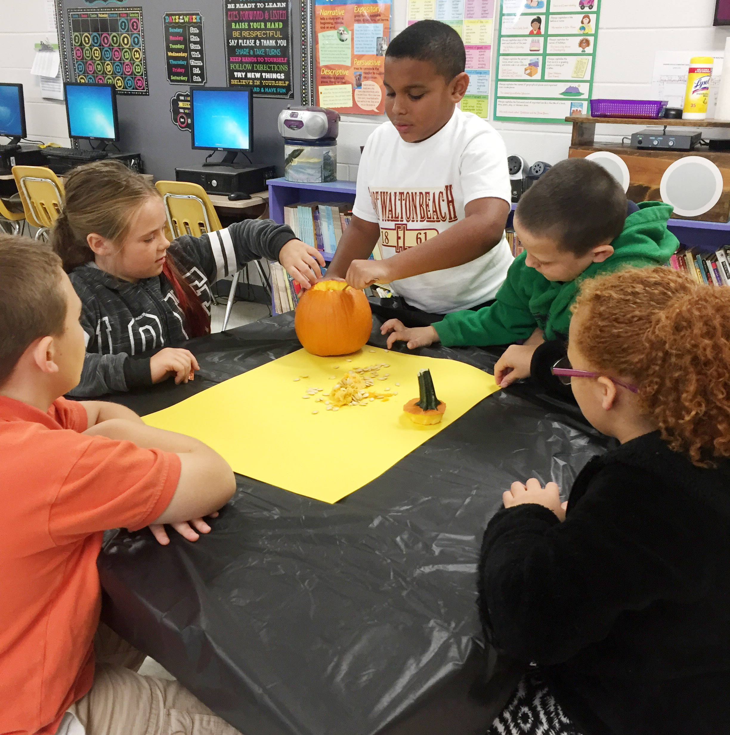 CES third-grader Zaemar Hoskins scoops seeds out of his group's pumpkin.