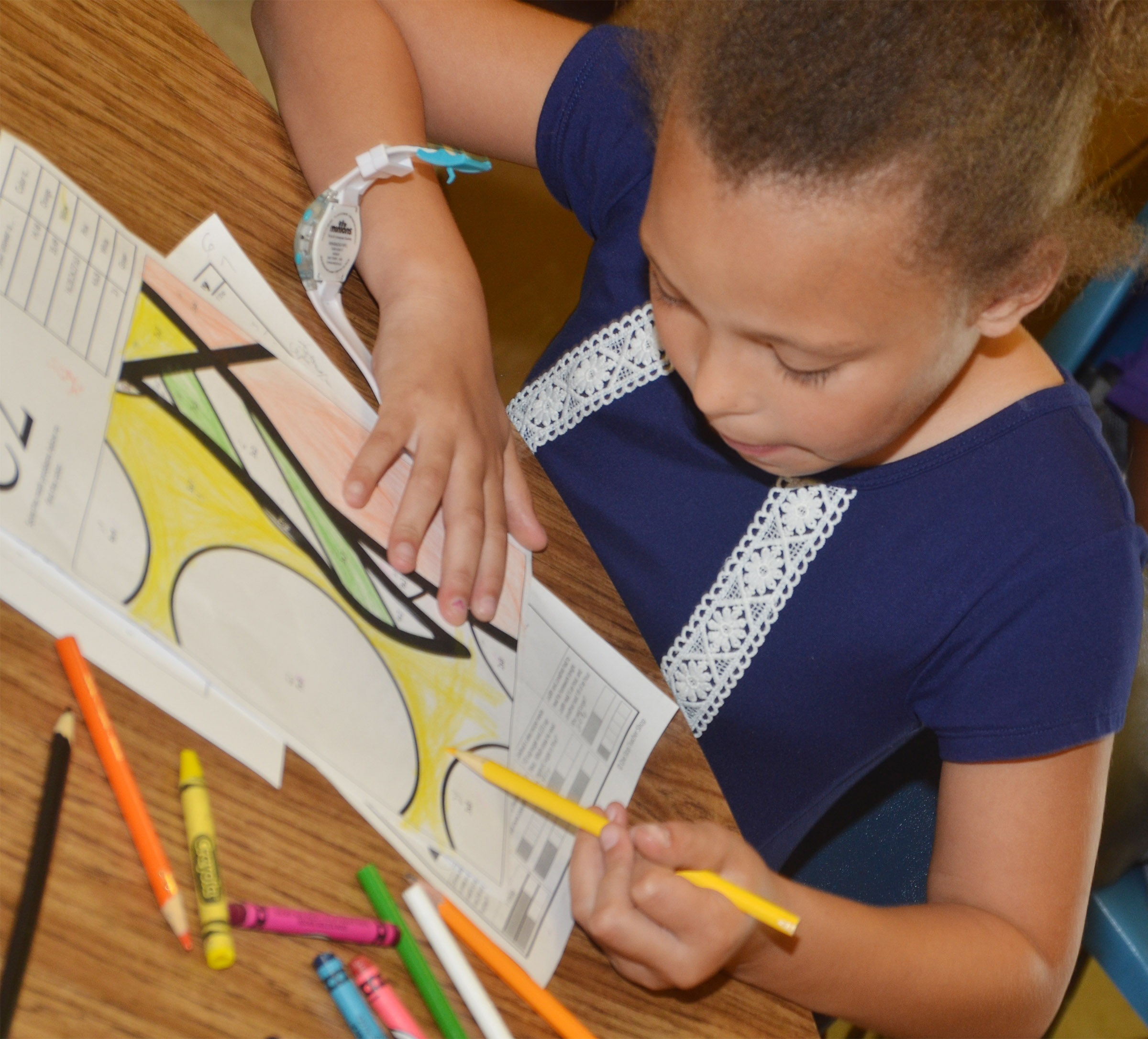 CES third-grader Alexis Graves colors her puzzle piece.