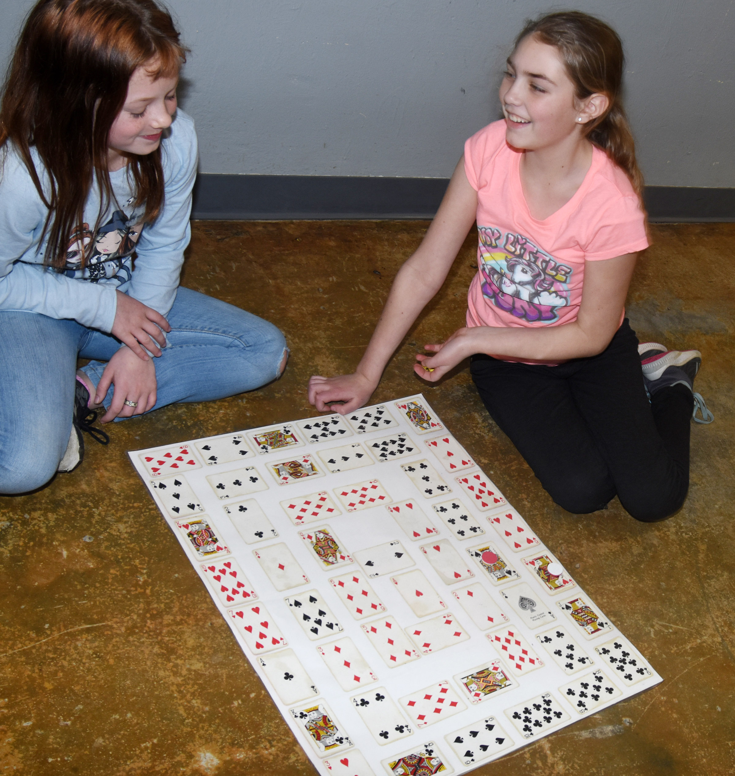CES fifth-graders Kyra Parker, at left, and Harley Couch-Allen play a card game to test their multiplication skills.