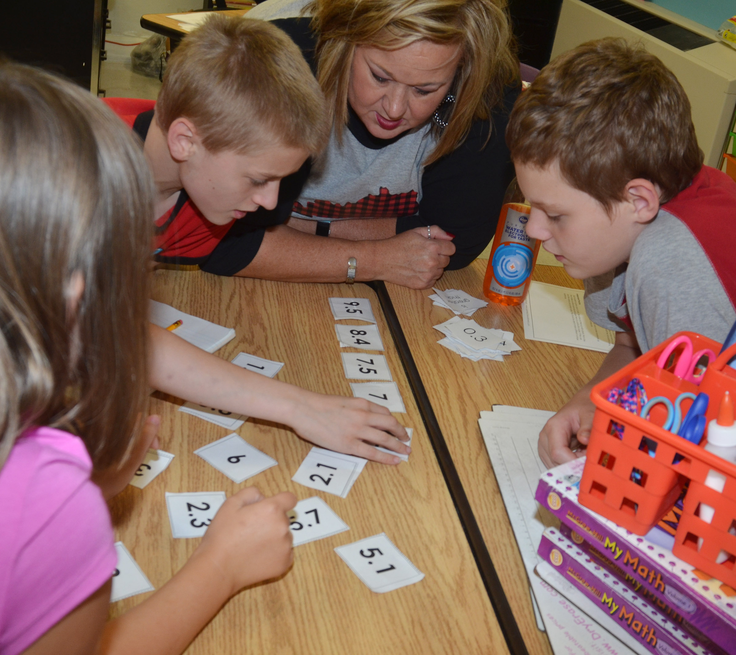 CES instructional assistant Kim Wagers helps fifth-graders Tre Shipione, at left, and Ethan Cox place numbers in order based on their value.