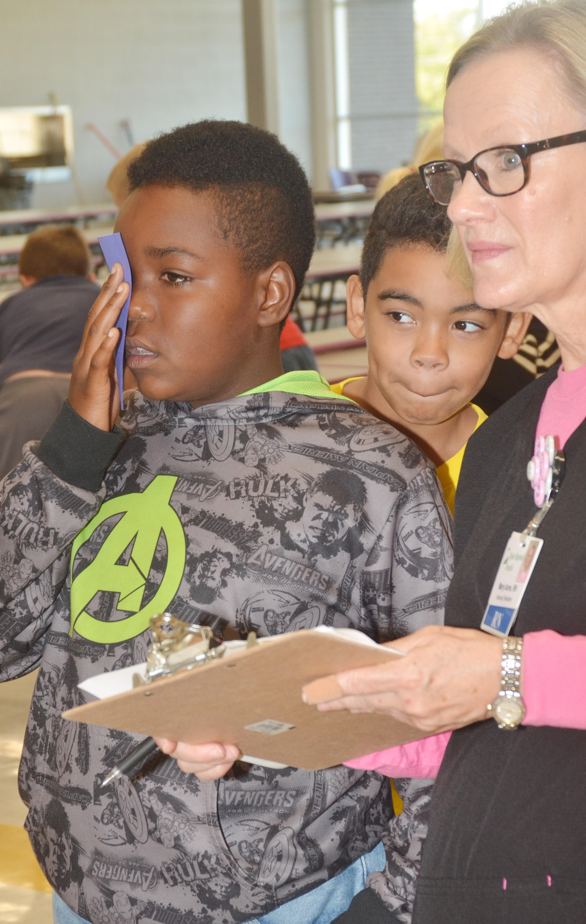 CES fifth-grader Deason Smith undergoes an eye exam with Mary Anne Rice, a registered nurse at Taylor Regional Hospital, as fifth-grader Gabriel Noyola waits his turn.