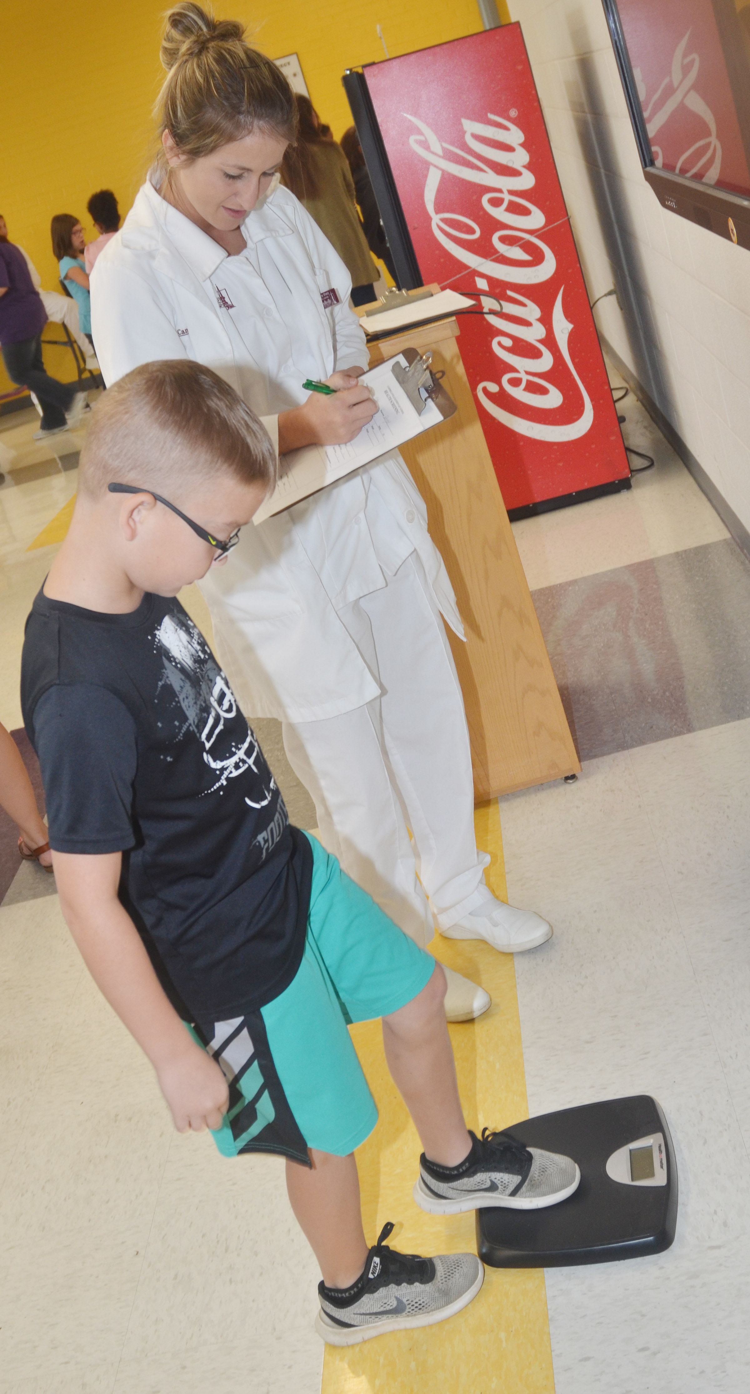 CES fourth-grader Cameron Estes weighs himself, with help from Campbellsville University nursing student Tiffany Sharp.