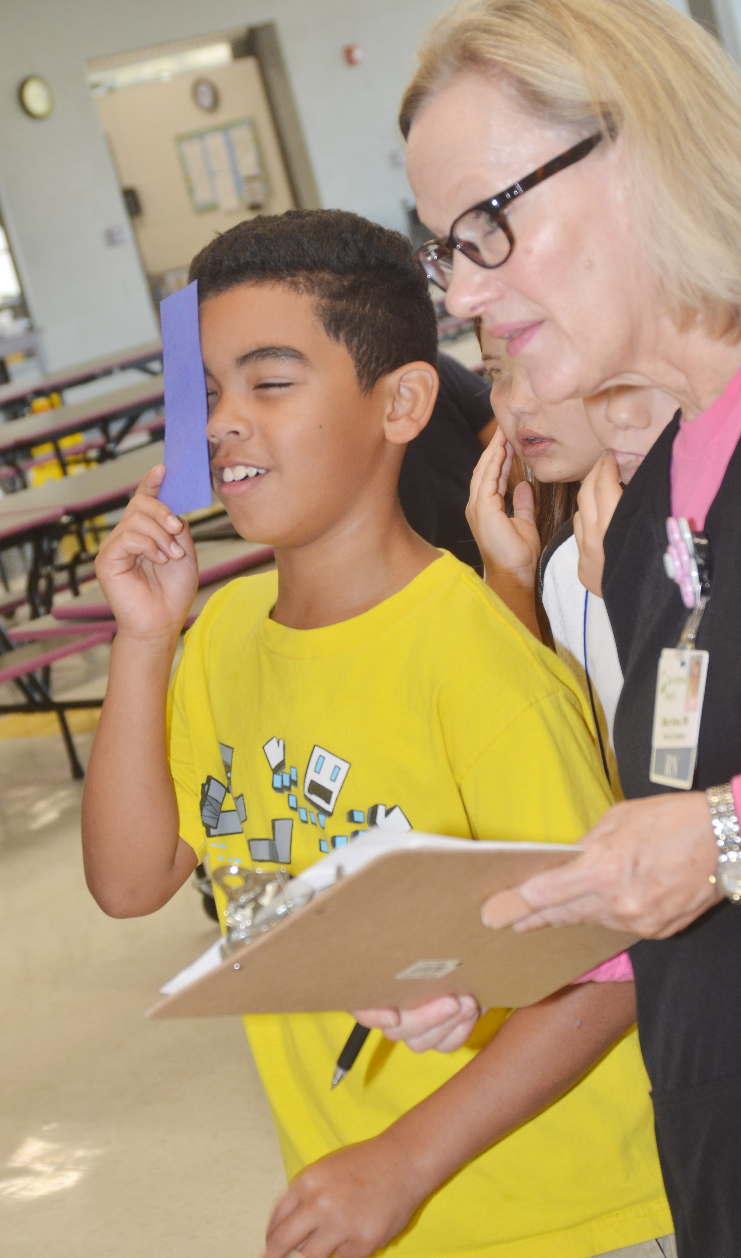 CES fifth-grader Gabriel Noyola undergoes an eye exam with Mary Ann Rice, a registered nurse at Taylor Regional Hospital.