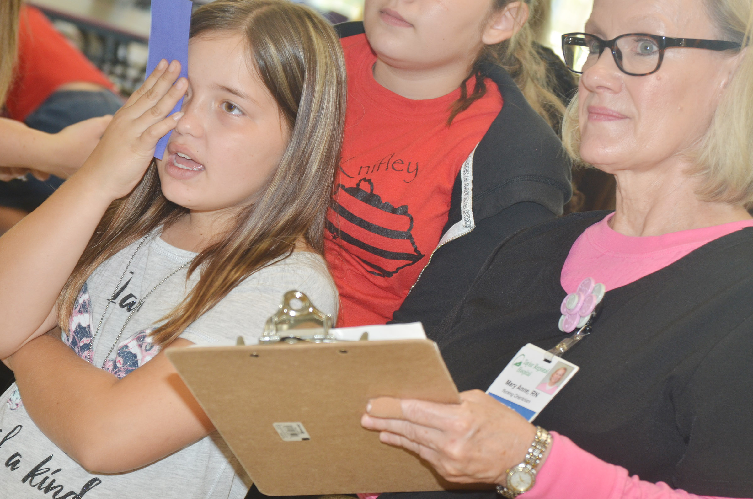 CES fifth-grader Kate Billeter undergoes an eye exam with Mary Ann Rice, a registered nurse at Taylor Regional Hospital.