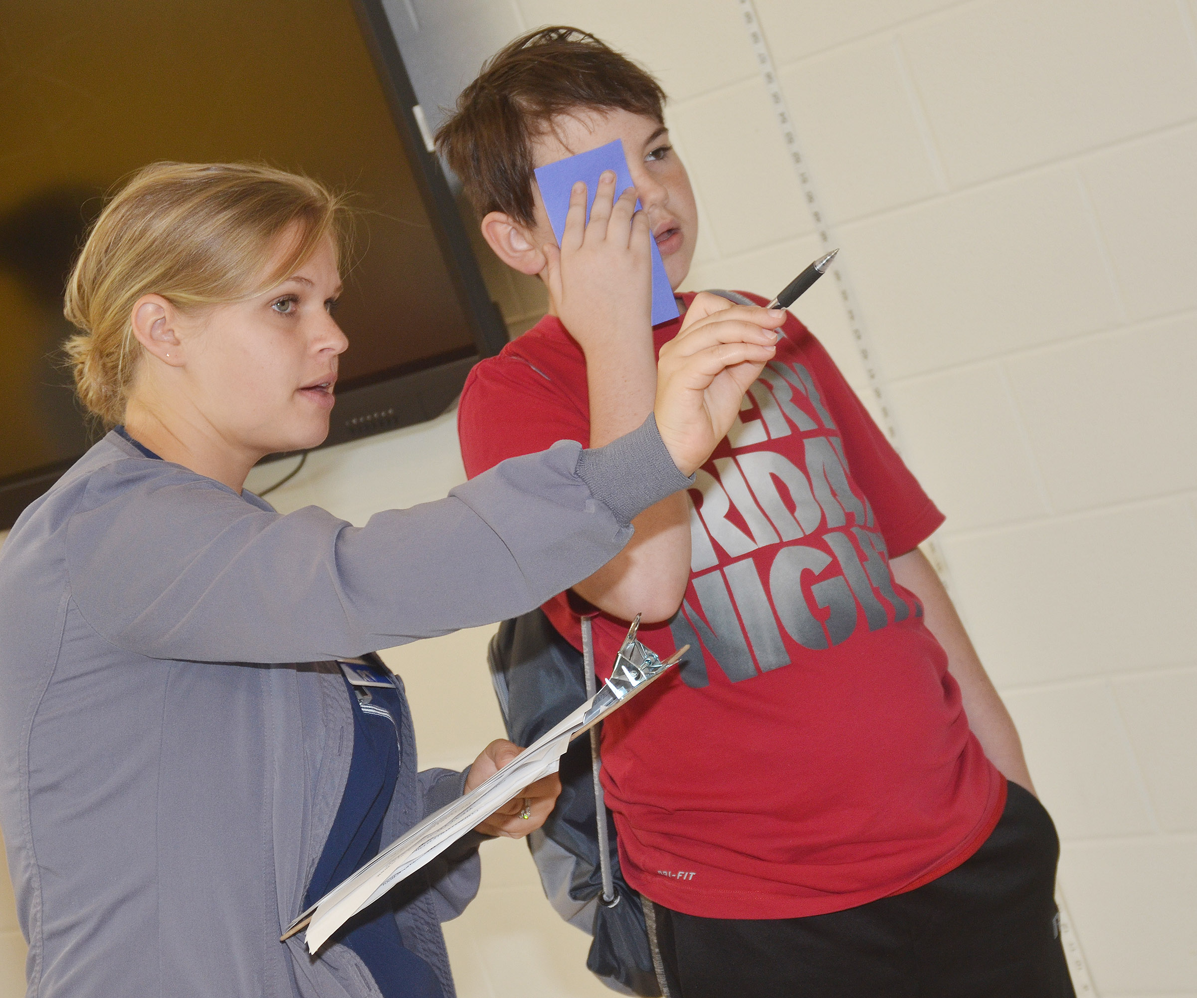 CES fifth-grader Cody Agee undergoes an eye exam with Brandie Adams, a registered nurse at Taylor Regional Hospital.