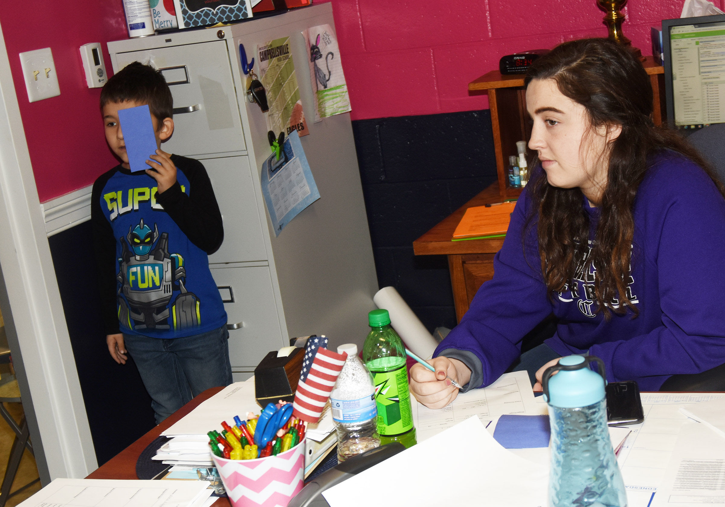 CES first-grader Josiah Edwards undergoes an eye exam, as CHS senior Caitlin Bright records the results. Bright is an intern with CES Guidance Counselor Beth Wiedewitsch.