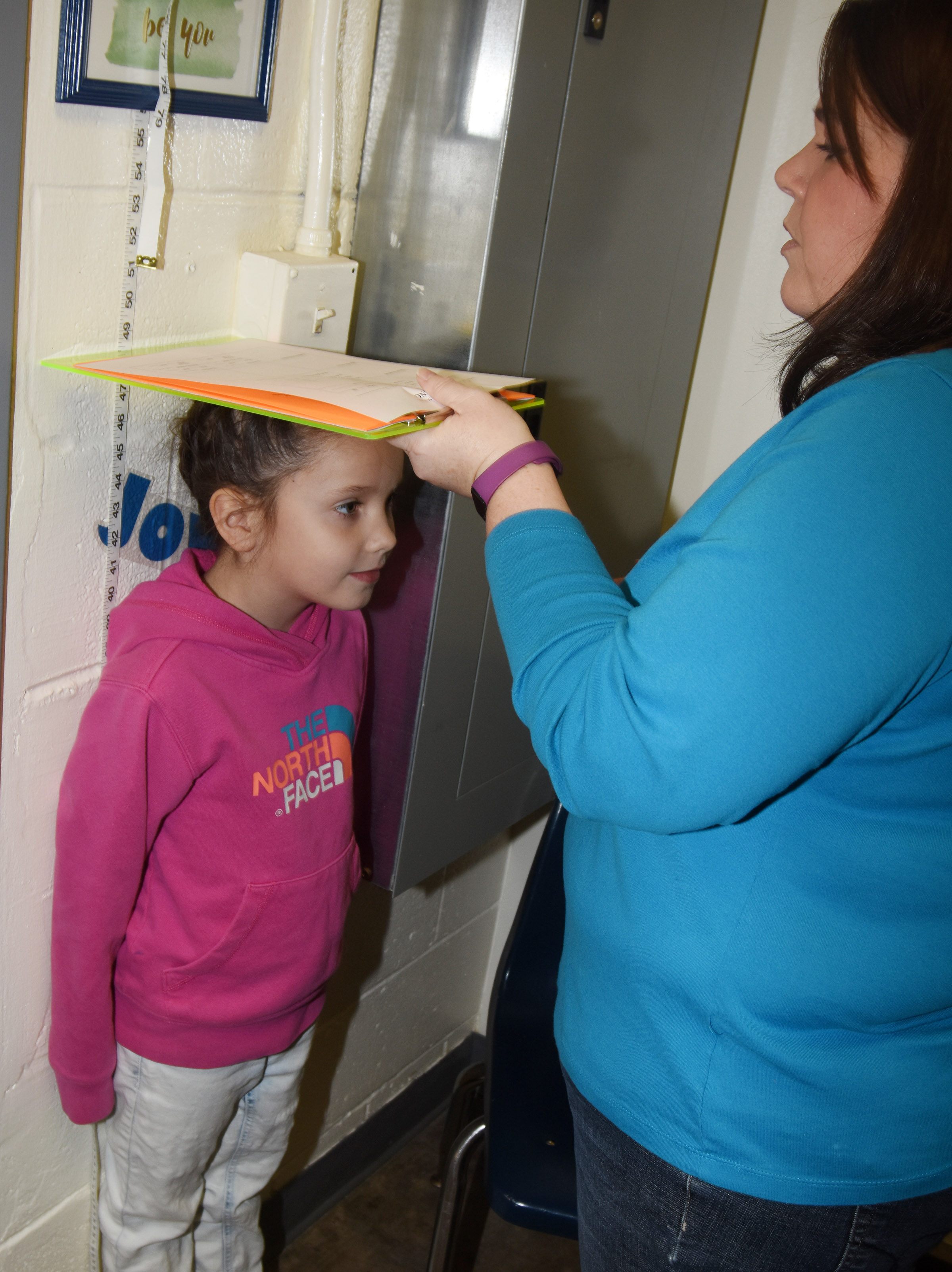 CES Guidance Counselor Beth Wiedewitsch measures first-grader Serenity Jones to see how much she has grown.