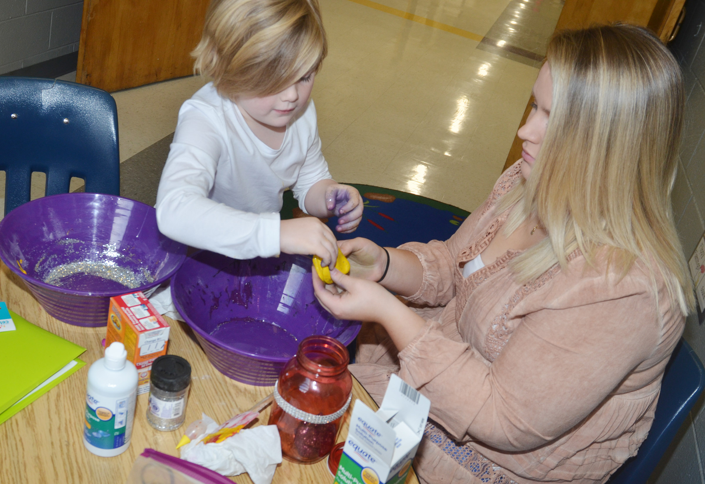 CHS graduate Heather Bailey makes slime with CES kindergartener Zoe Scharbrough.