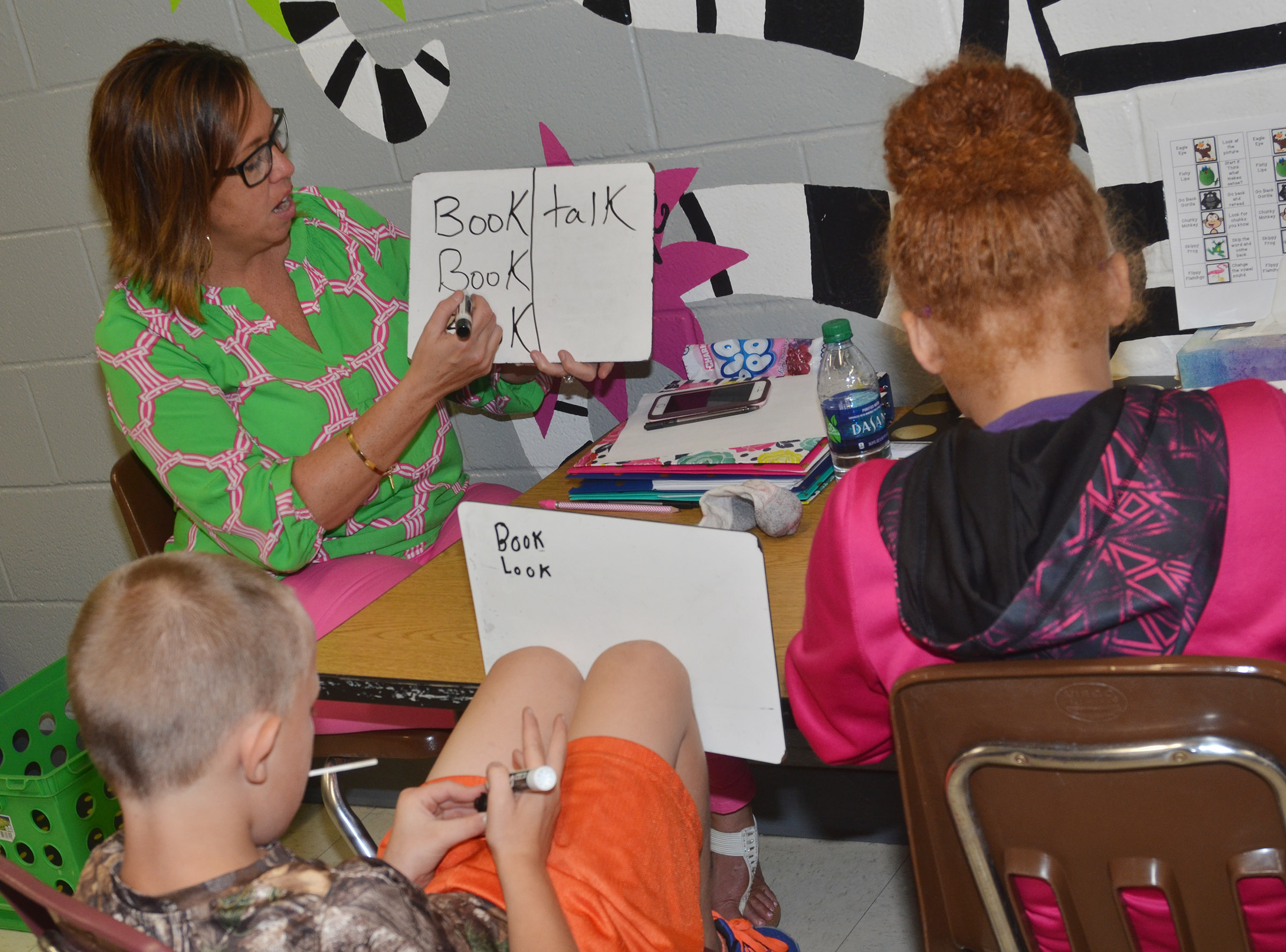 CES writing interventionist Farrah Hord helps third-graders Tyler Brown, at left, and Kallie Taylor write compound words.
