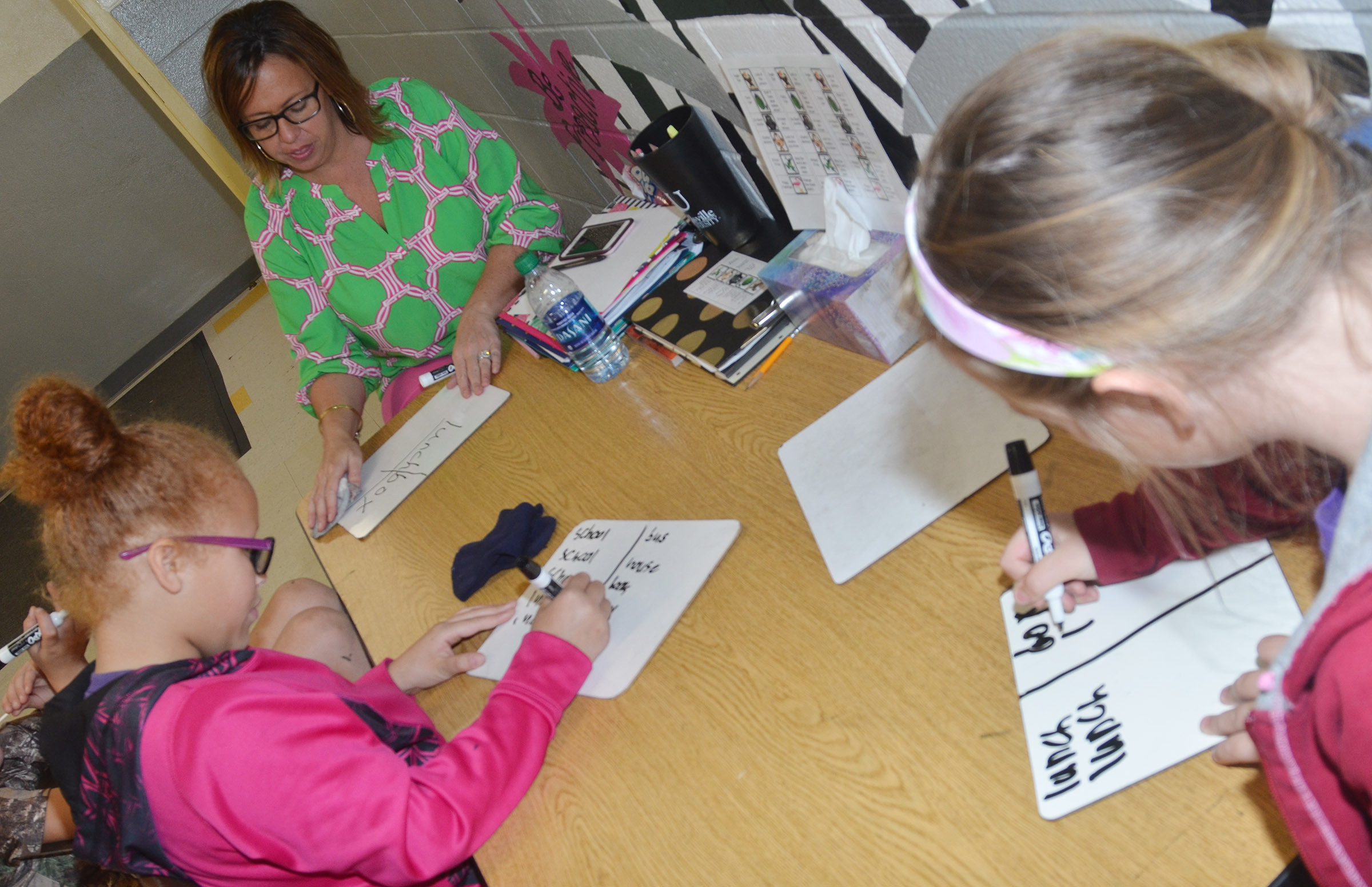 CES writing interventionist Farrah Hord helps third-graders Kallie Taylor, at left, and Caleigh Underwood write compound words.