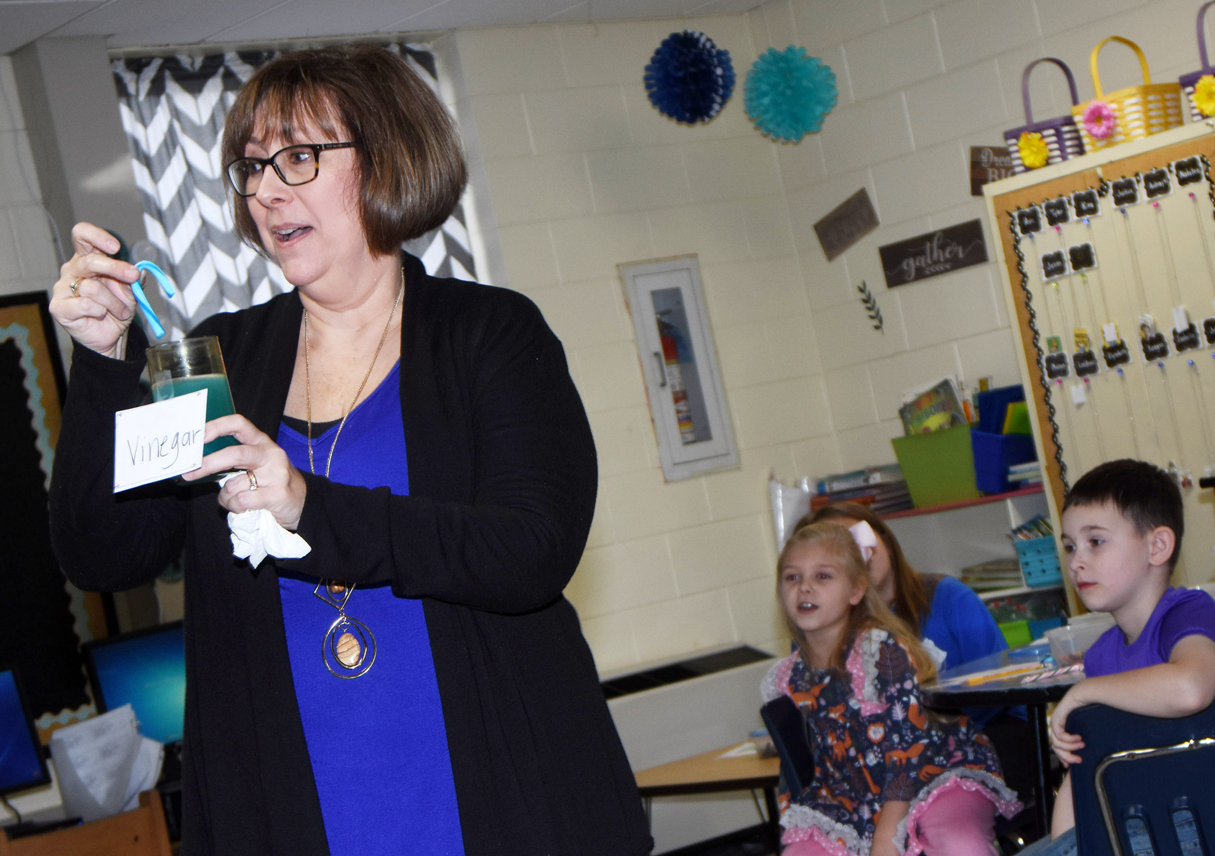 CES second-grade teacher Lynne Horn places a candy cane in vinegar to show her students the reaction.