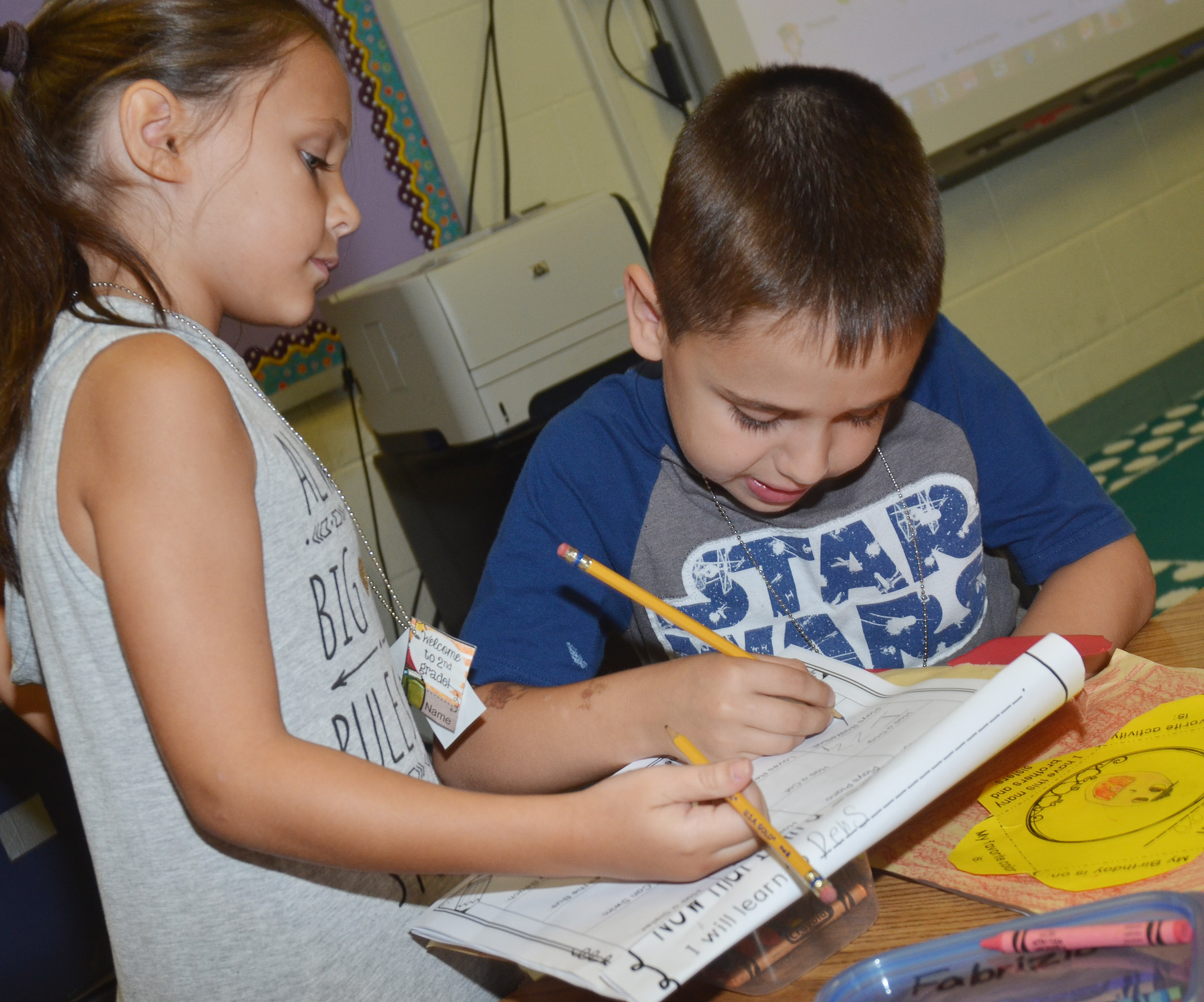 CES second-graders Serenity Taylor, at left, and Aaron Floyd sign each other's worksheets as they get to know each other.