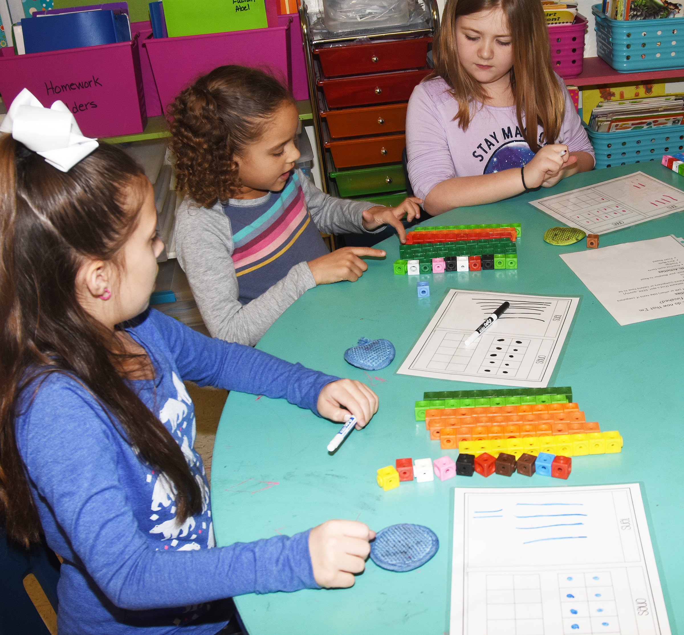 From left, CES second-graders Lillian Martin, Keiava Thompson and Frehley Whitlow add by using regrouping.
