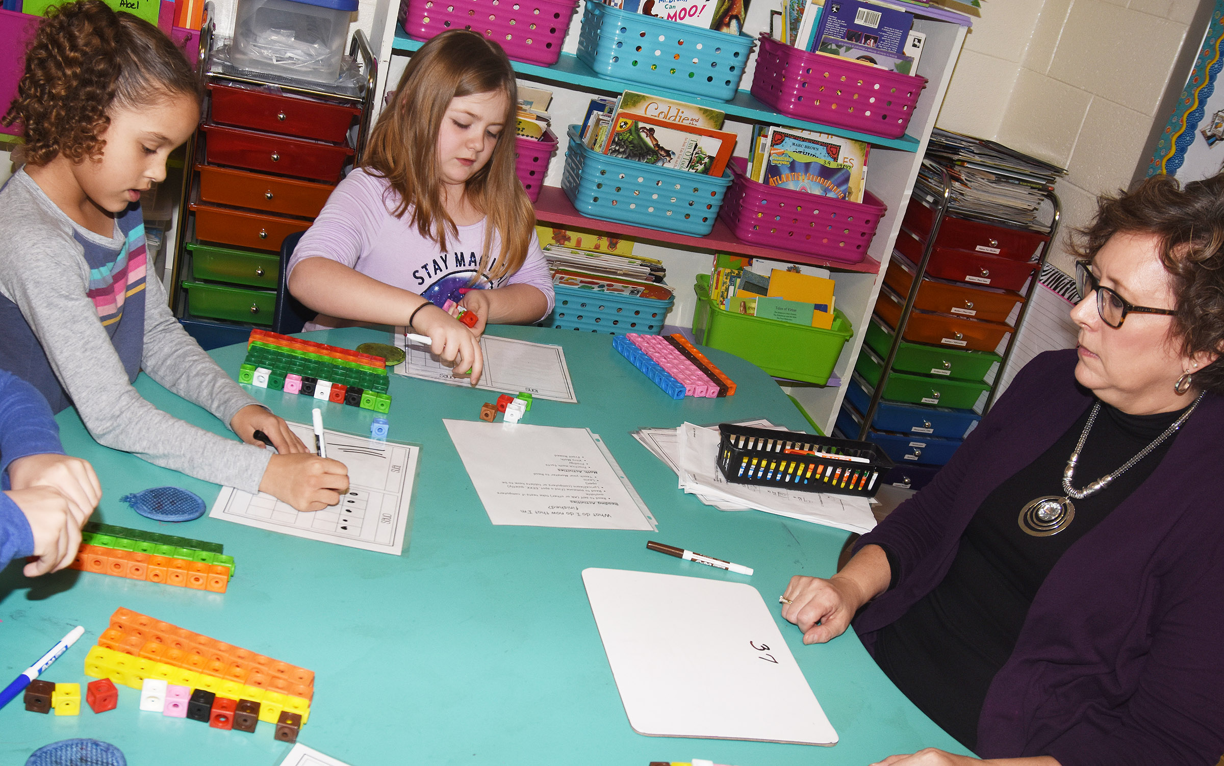 CES second-grade teacher Lynne Horn helps second-graders Keiava Thompson, at left, and Frehley Whitlow add by using regrouping.