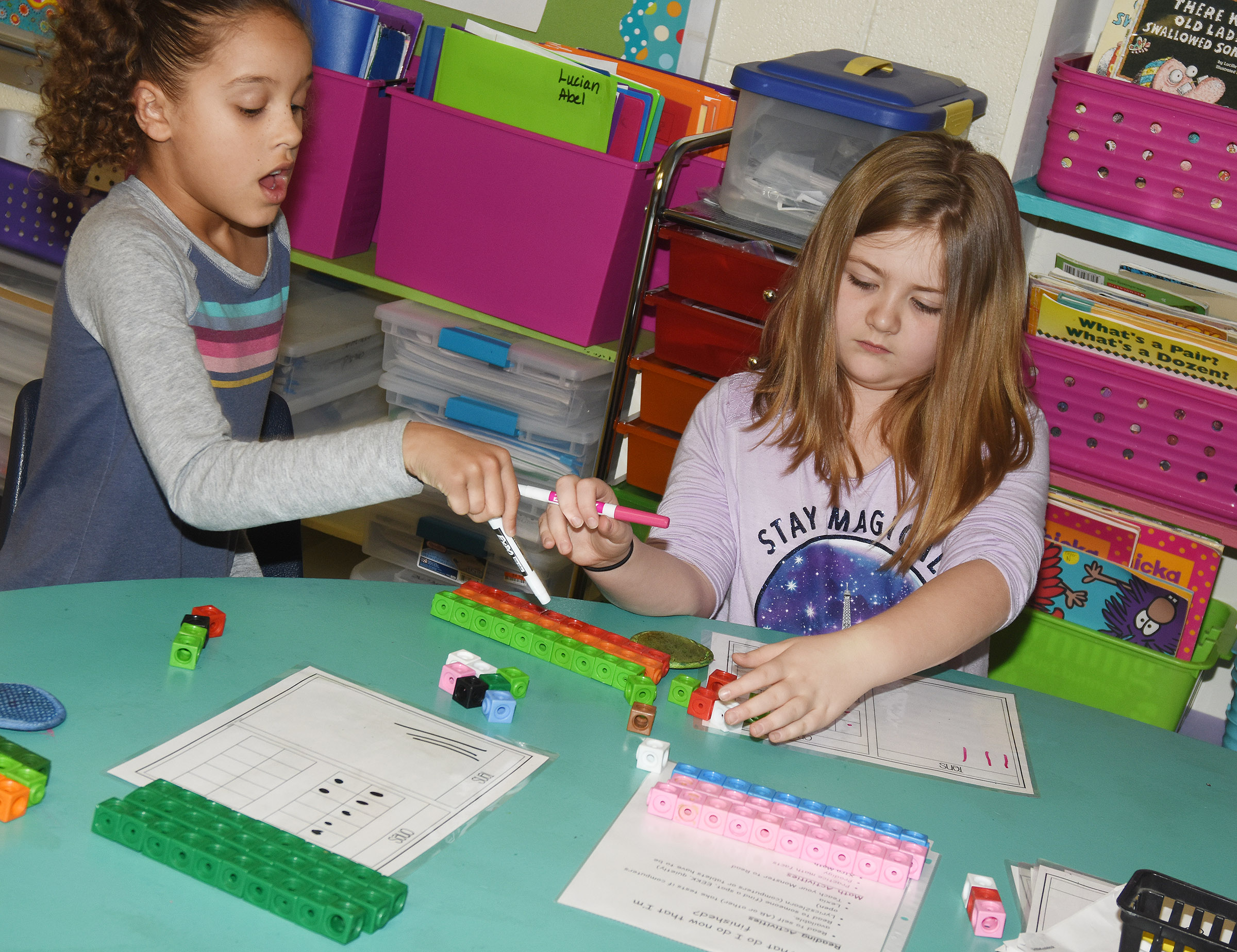 CES second-graders Keiava Thompson, at left, and Frehley Whitlow work together to add by using regrouping.