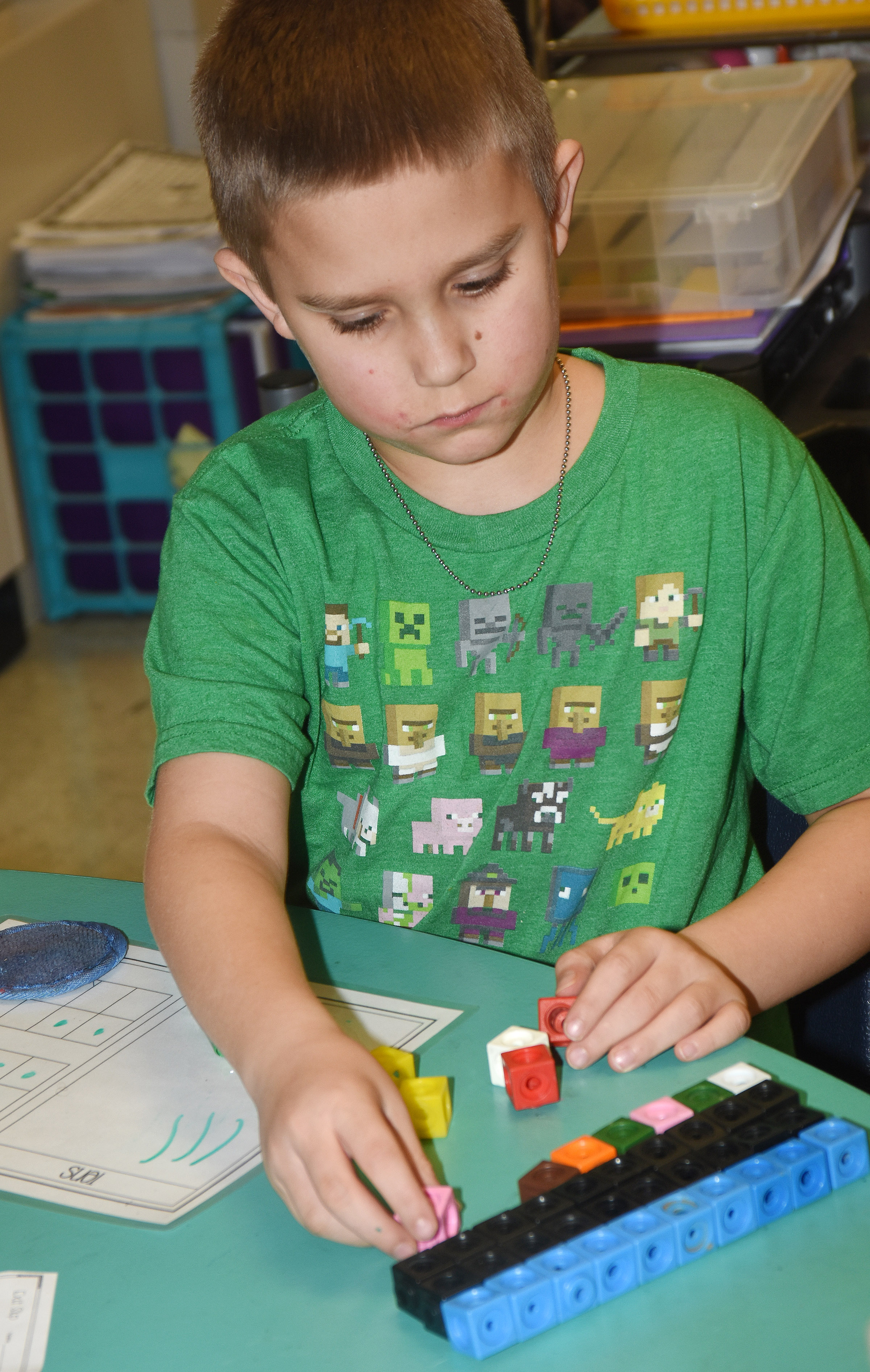 CES second-grader Nikolas Torres adds by using regrouping.