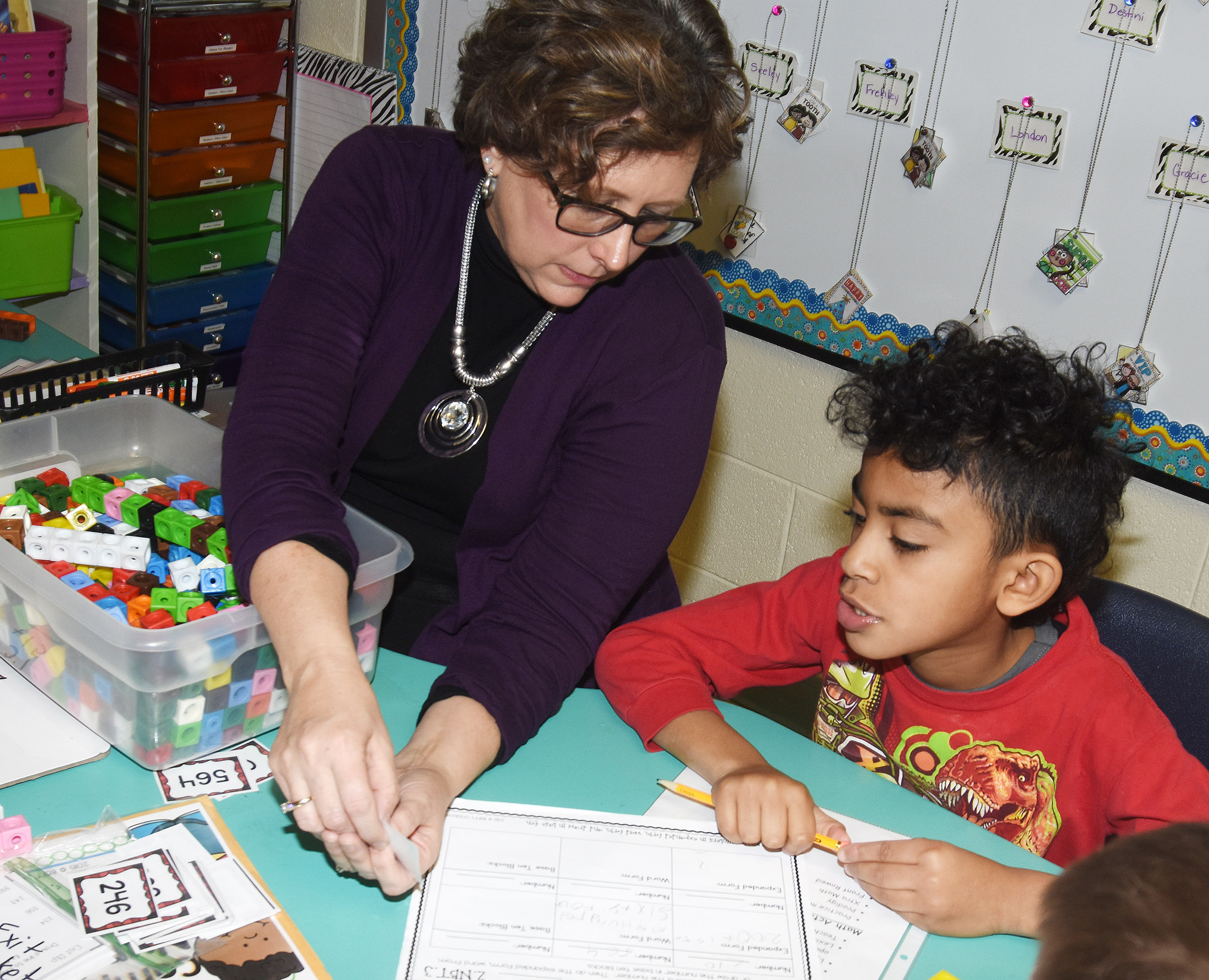 CES second-grade teacher Lynne Horn helps Enoch Smith with addition.