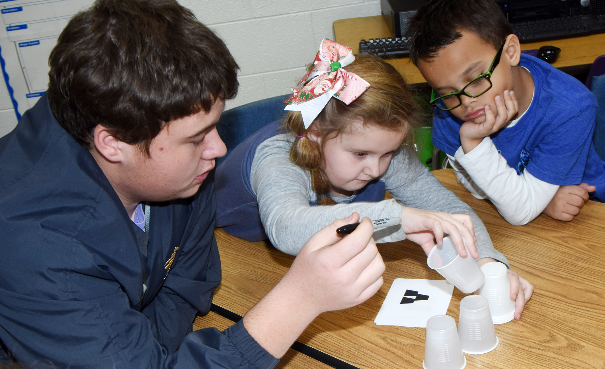 CHS junior Conner Riley helps CES second-graders Laurna McKenzie, center, and Davian Taylor as they portray robots and follow a computer code.