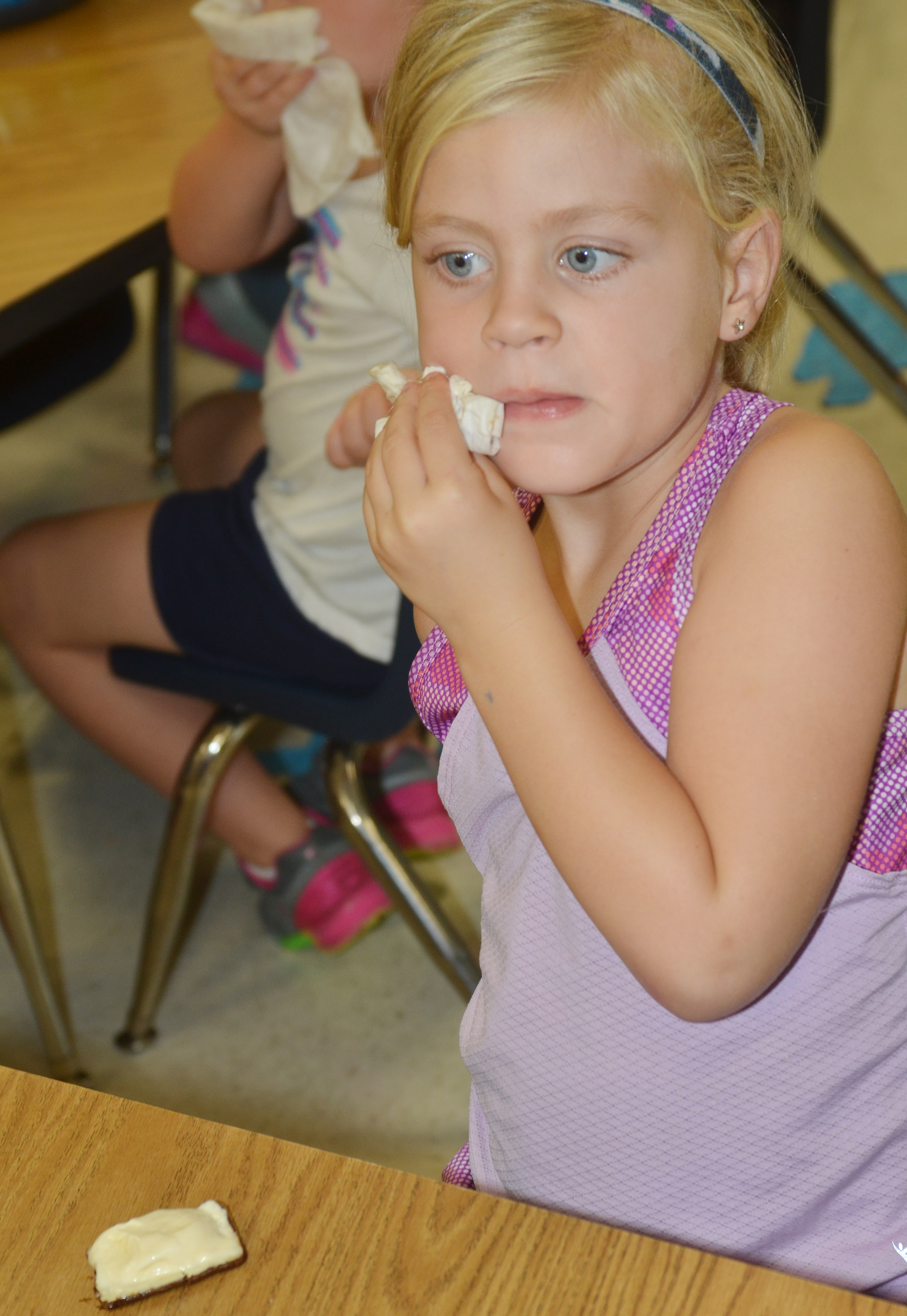 CES kindergartener Remi Petett wipes her mouth as she enjoys her ice cream sandwich.