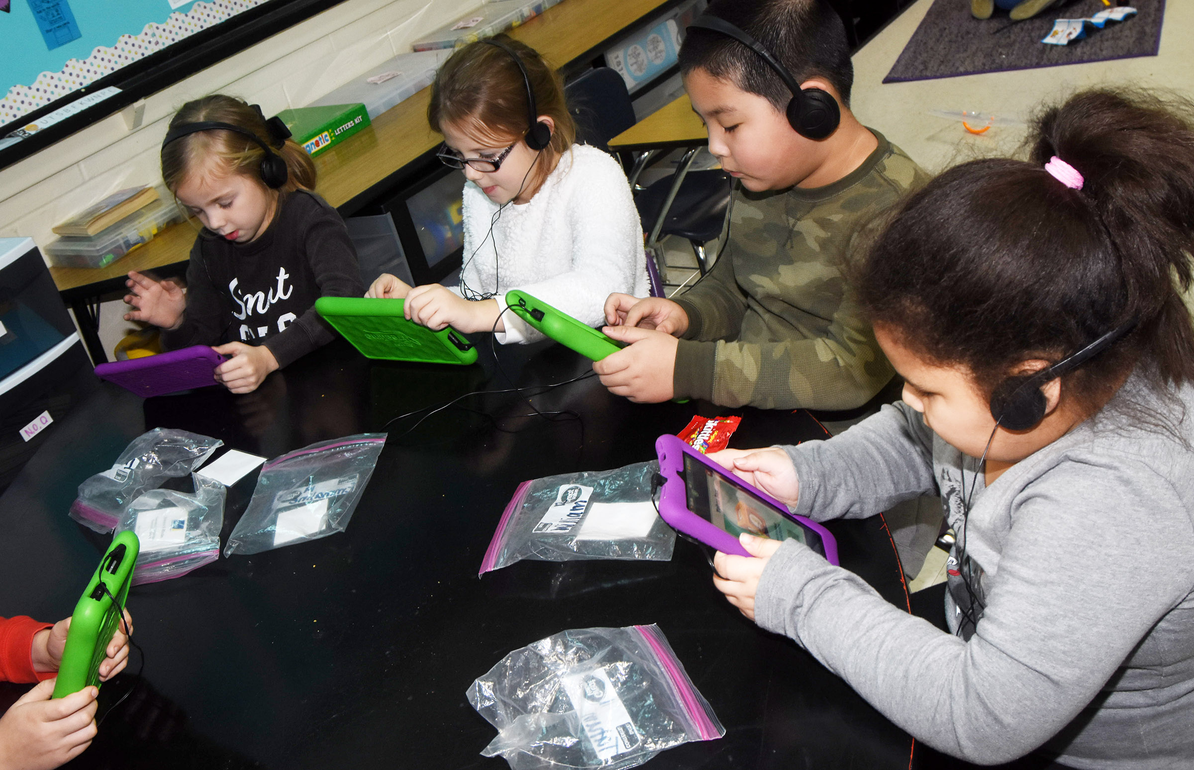 From left, CES first-graders Trinidy Gribbins, Bailey Freeman, William Li and Tatum Hoskins play games on their tablets.