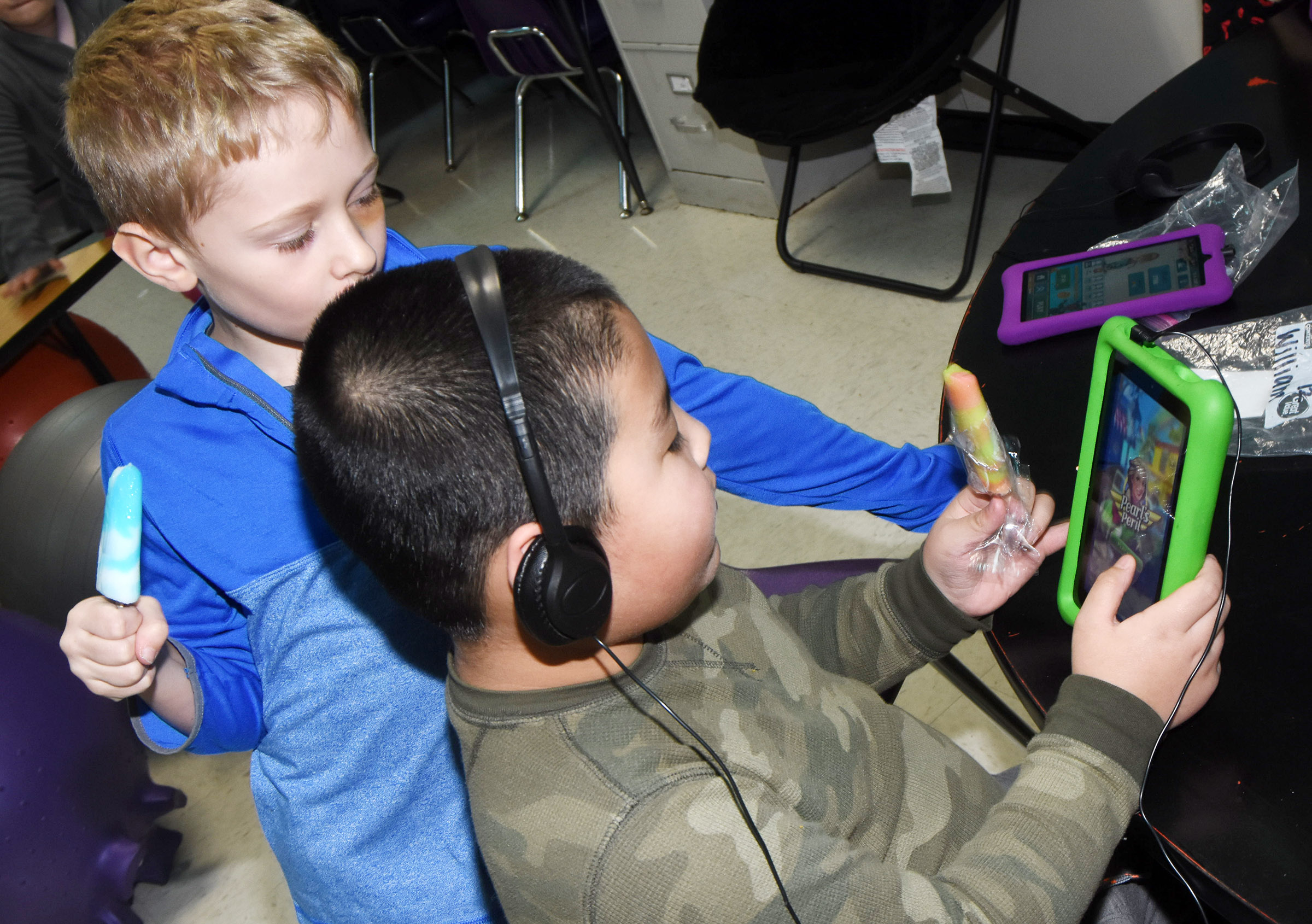 CES first-graders Jackson Wright, at left, and William Li enjoy popsicles as they play a game together on a tablet.