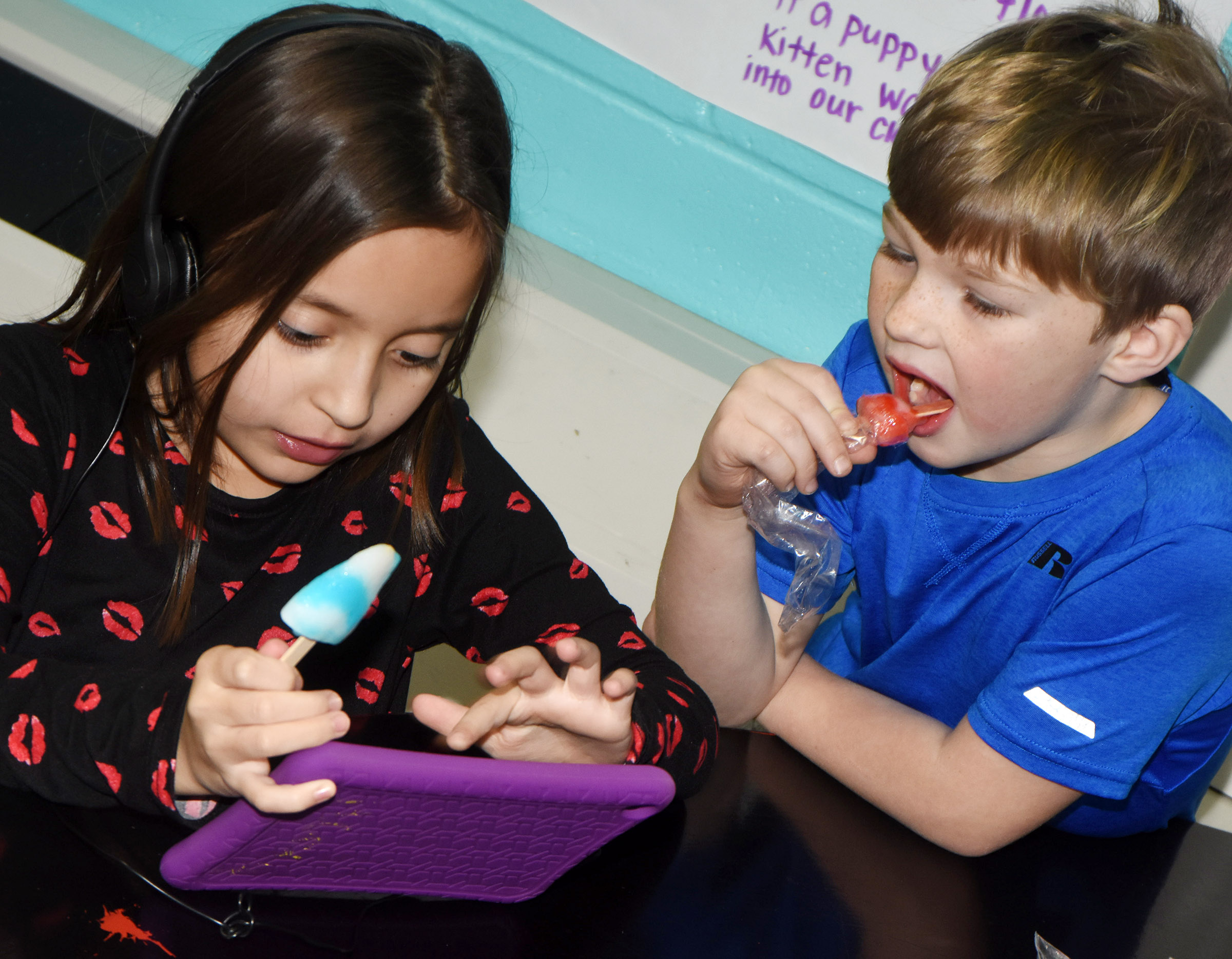 CES first-graders Gabriella Tate, at left, and Landry Brown enjoy popsicles together as they play games on a tablet.