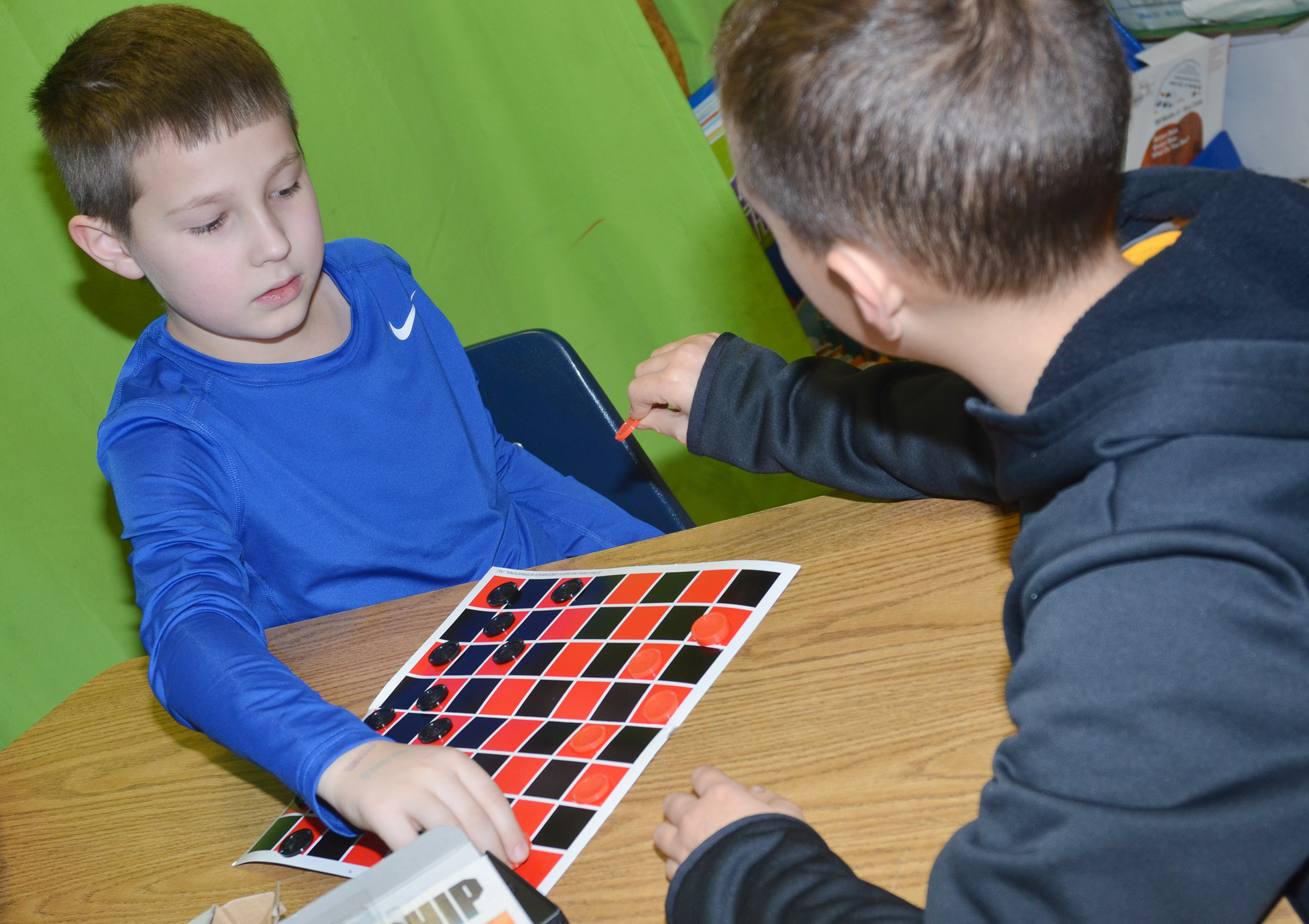CES third-grader Grayson Dooley plays checkers with his classmate.