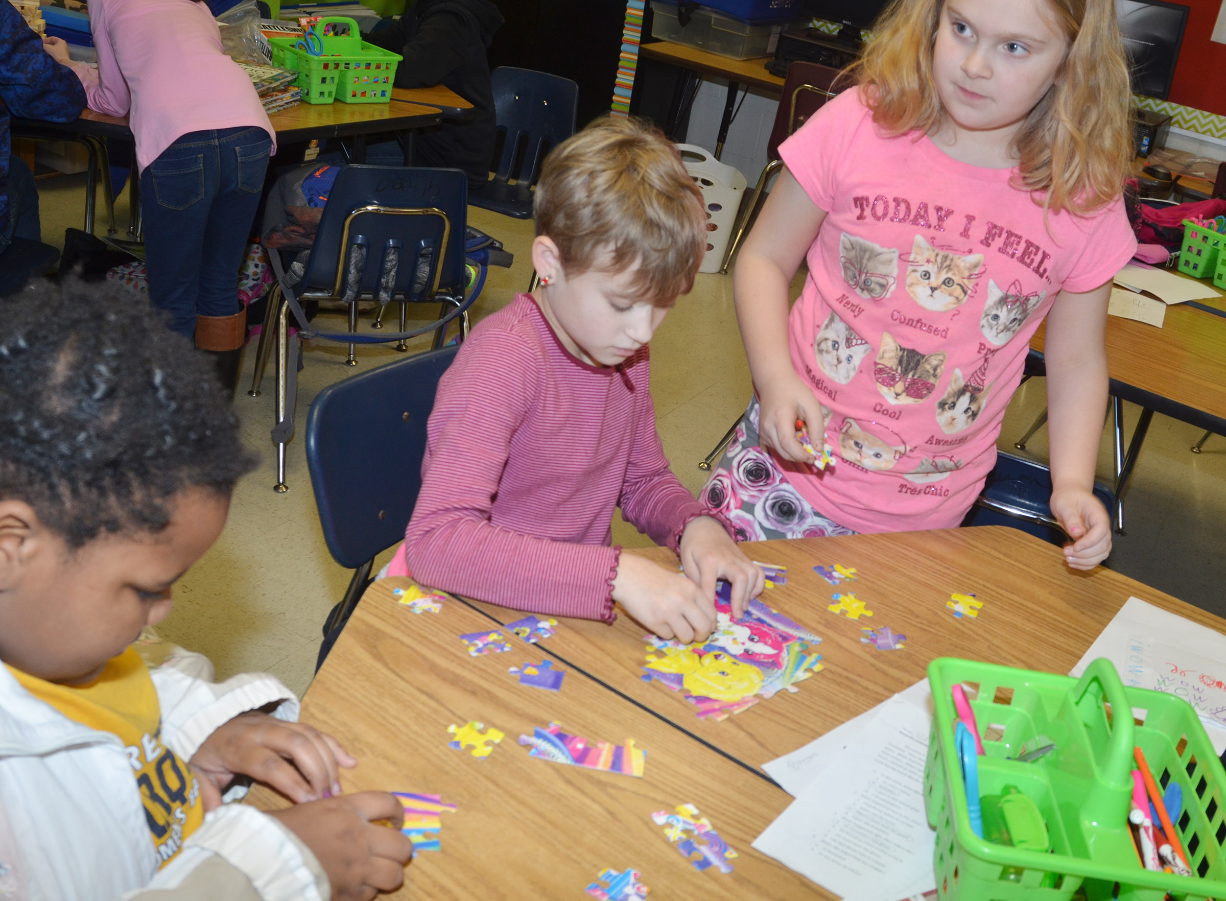 From left, CES third-graders Talaysia Daniels, Katie Nunn and Arianna Childers put a puzzle together.